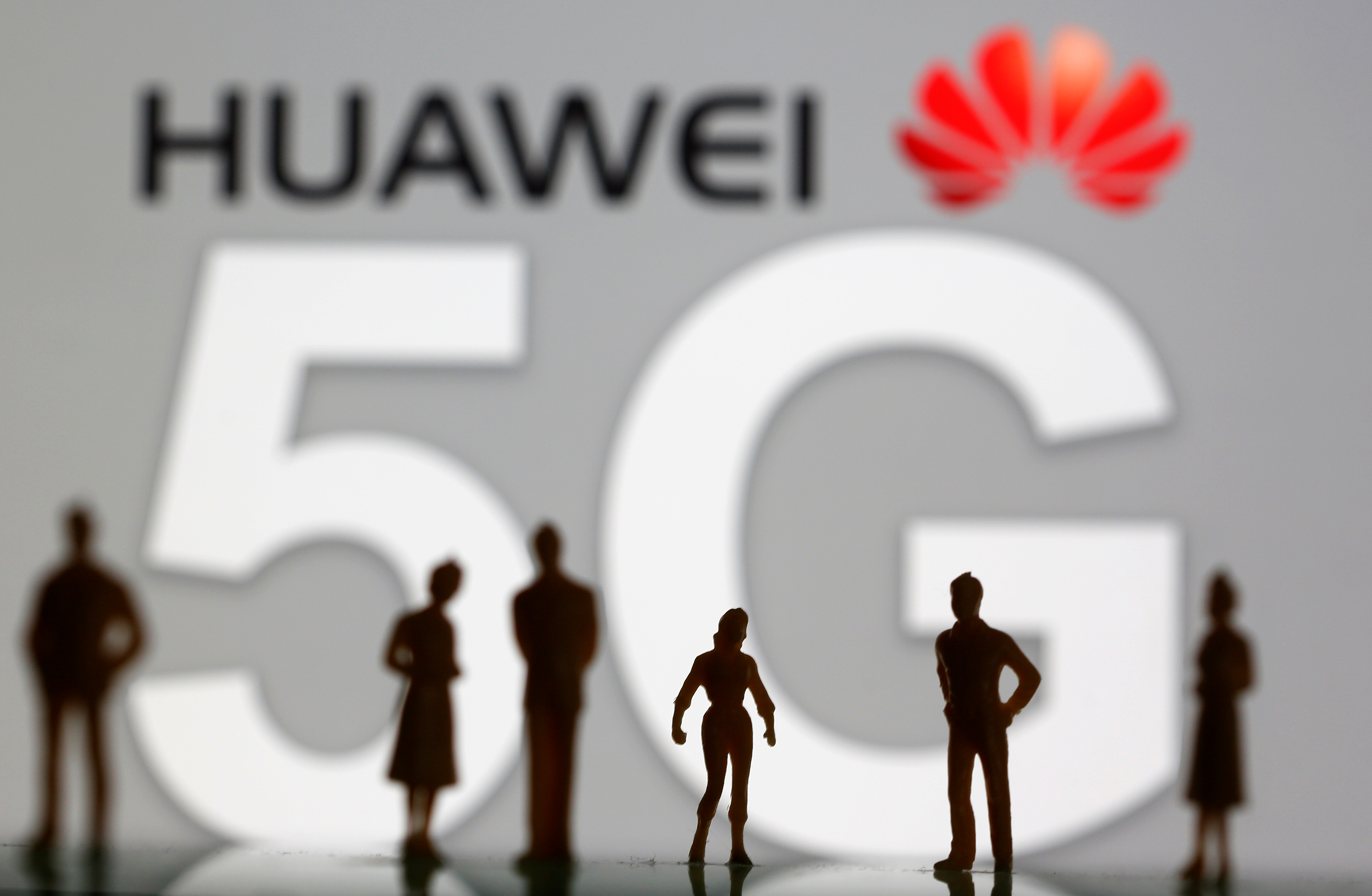 Small toy figures are seen in front of a displayed Huawei and 5G network logo in this illustration picture, March 30, 2019. REUTERS/Dado Ruvic/Illustration