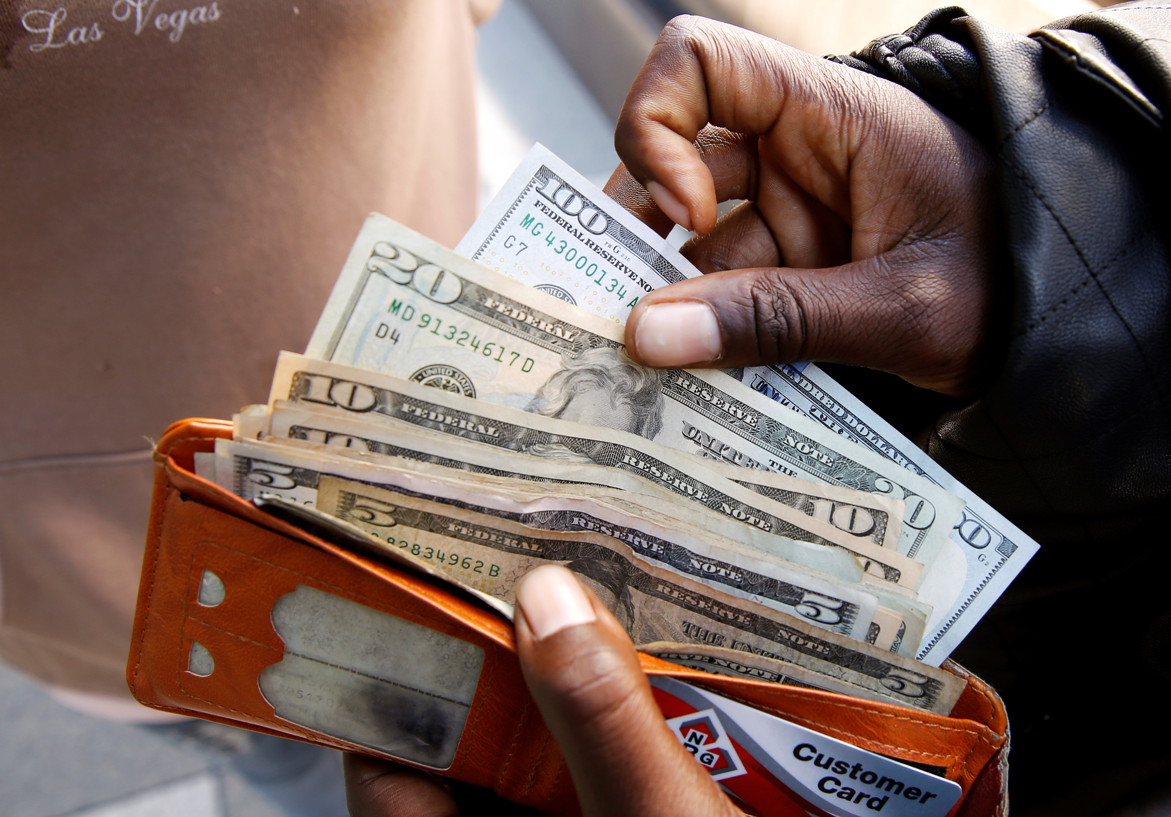 A man displays US dollar notes after withdrawing cash from a bank in Harare, Zimbabwe,  July 9, 2019. REUTERS/Philimon Bulawayo