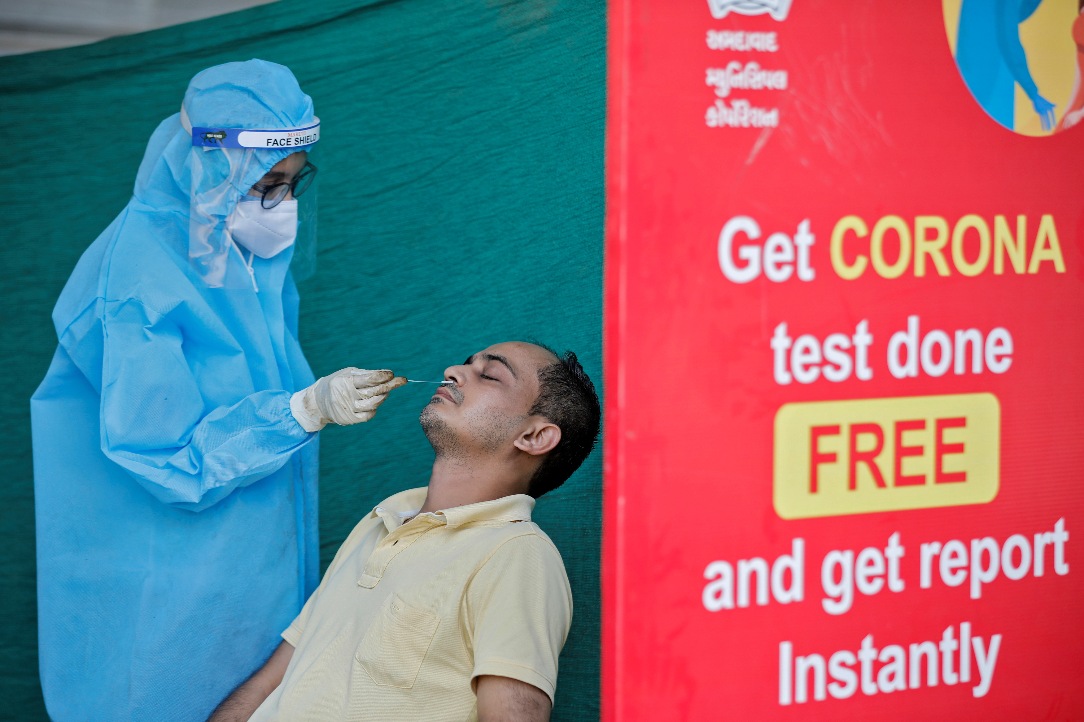 A healthcare worker wearing personal protective equipment (PPE) takes swab from a man during a testing campaign for the coronavirus disease (COVID-19), in Ahmedabad, India November 24, 2020. REUTERS/Amit Dave