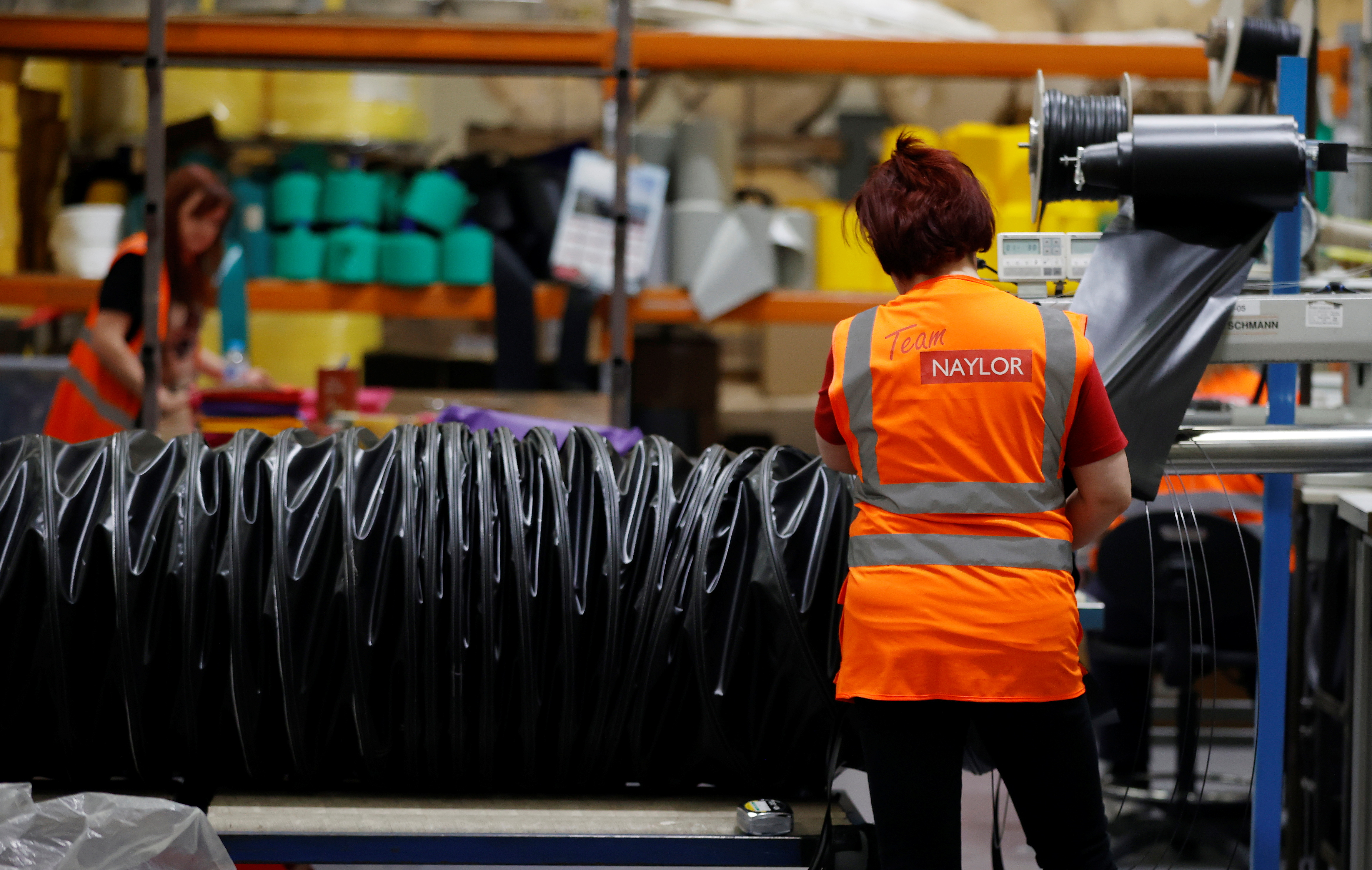 A worker constructs a length of ducting tube inside the Naylor Industries Wombwell site in Wombwell, Britain, April 27, 2021. Picture taken April 27. REUTERS/Phil Noble