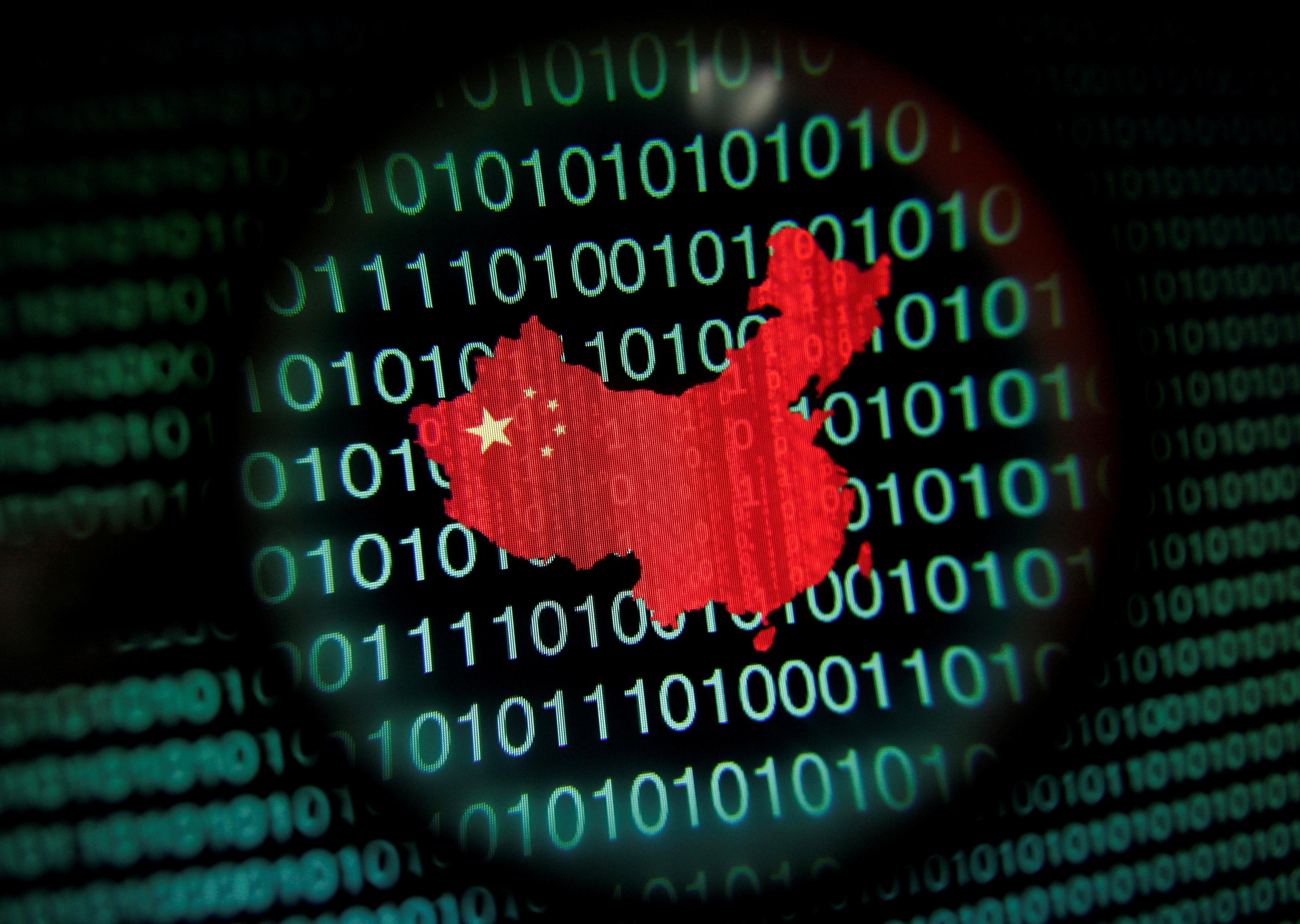 Une carte de la Chine est vue à travers une loupe sur un écran d'ordinateur montrant des chiffres binaires à Singapour dans cette illustration photo du 2 janvier 2014.  Photo prise le 2 janvier 2014. REUTERS/Edgar Su/File Photo