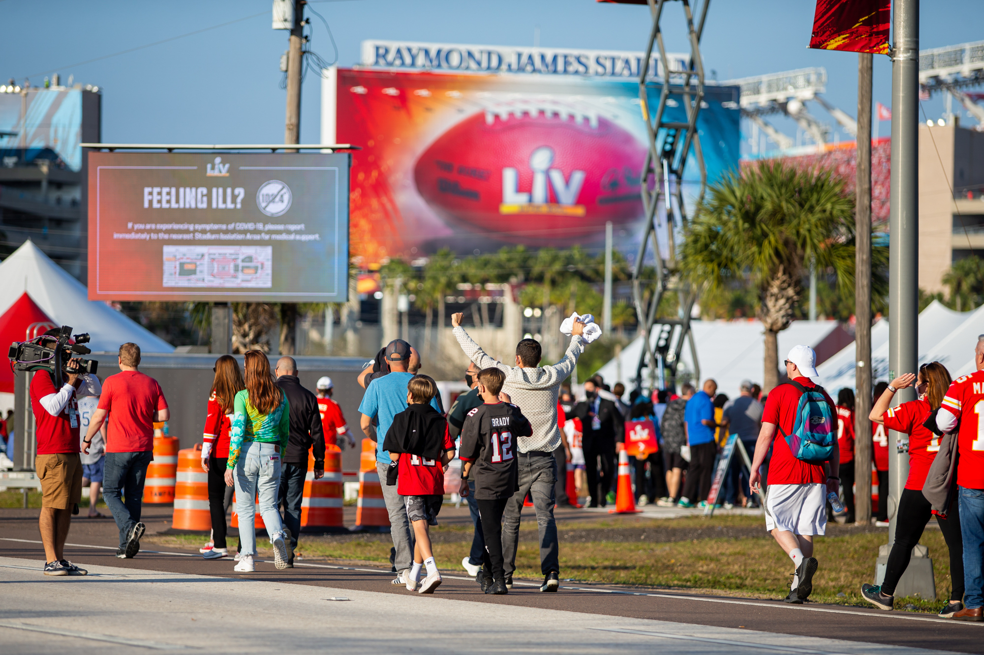 Feb 7, 2021; Tampa, Florida, USA; Fans approach Raymond James Stadium under COVID precautionary signage before Super Bowl LV between the Kansas City Chiefs and the Tampa Bay Buccaneers in Tampa, FL.  / Mary Holt-USA TODAY Sports/File Photo