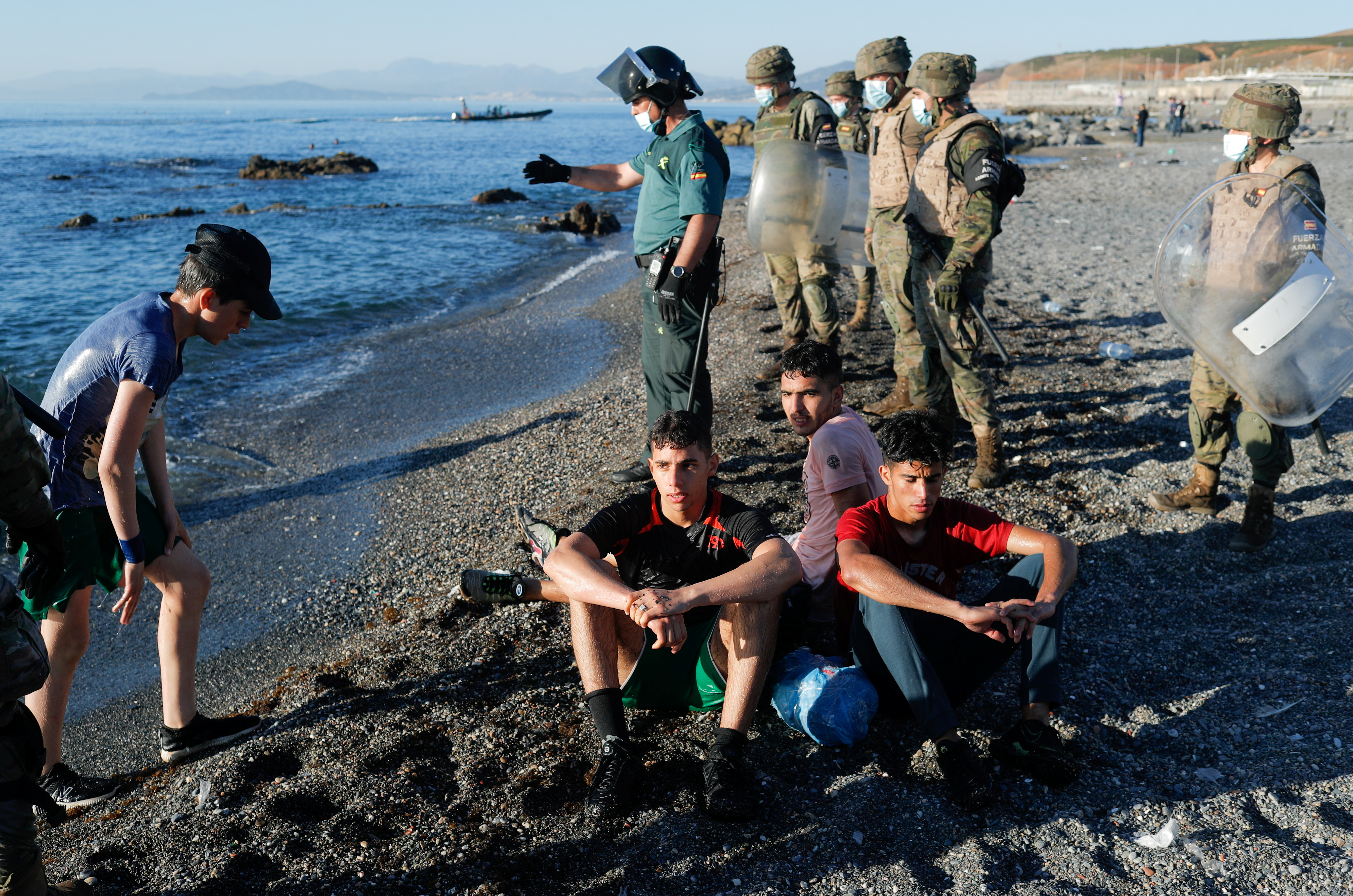 Spanish soldiers stand guard as Moroccan citizens sit at El Tarajal beach, near the fence between the Spanish-Moroccan border, after thousands of migrants swam across the border, in Ceuta, Spain, May 19, 2021. REUTERS/Jon Nazca