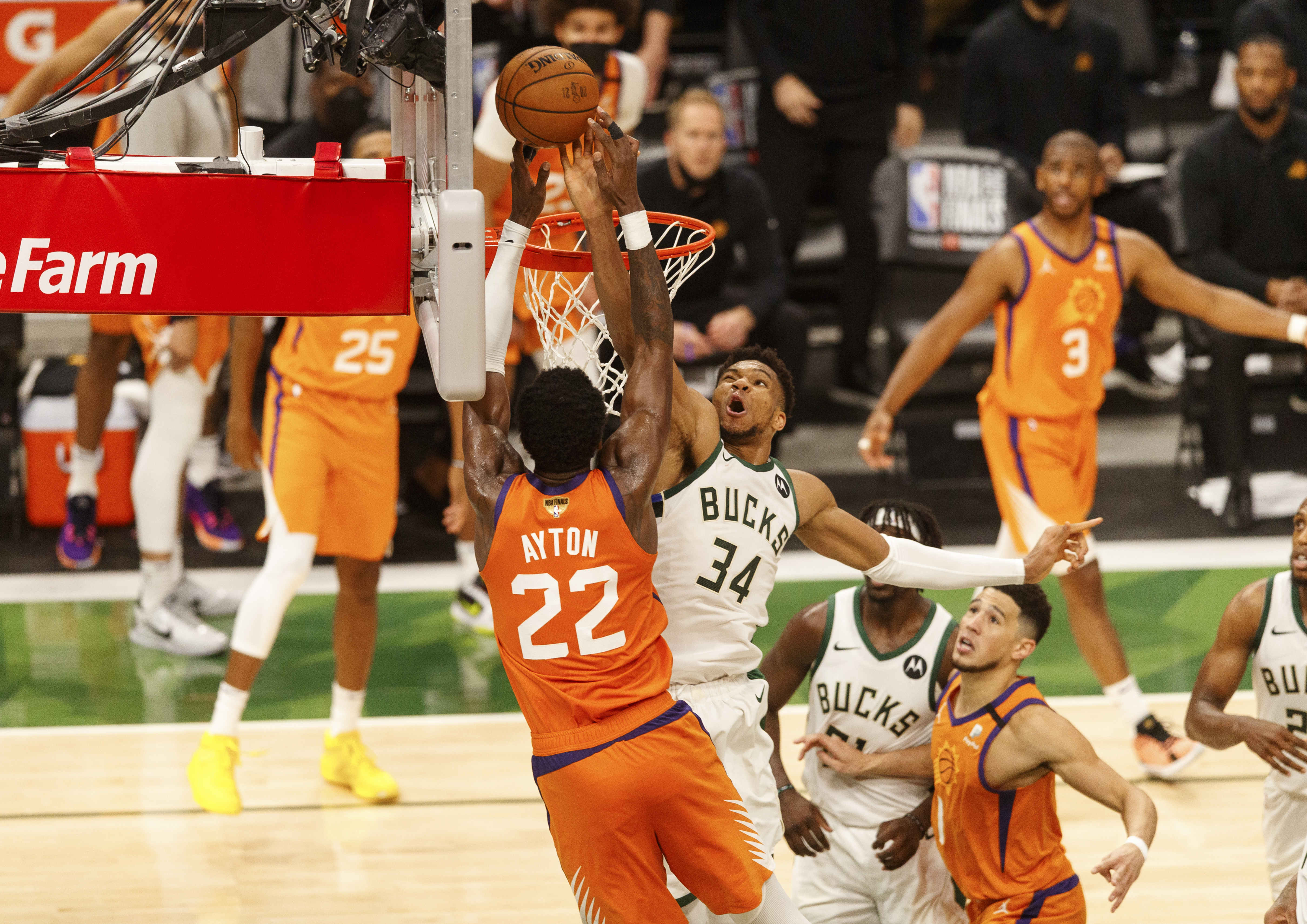 Jul 14, 2021; Milwaukee, Wisconsin, USA; Milwaukee Bucks forward Giannis Antetokounmpo (34) defends Phoenix Suns center Deandre Ayton (22) during the fourth quarter during game four of the 2021 NBA Finals at Fiserv Forum. Mandatory Credit: Jeff Hanisch-USA TODAY Sports