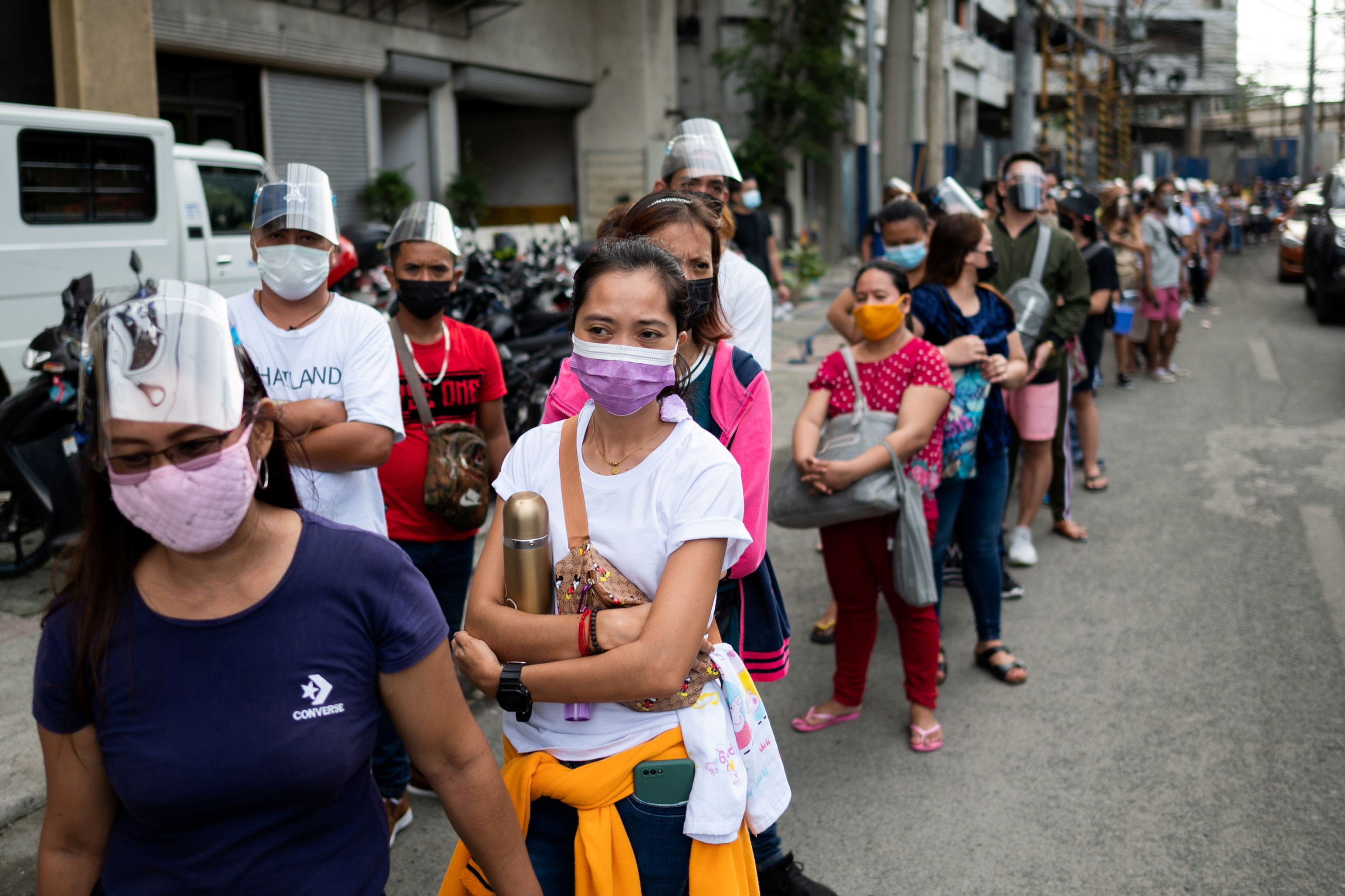 Filipinos waiting to be vaccinated against the coronavirus disease (COVID-19) queue outside a mall, a day before stricter lockdown measures are implemented, in Manila, Philippines, August 5, 2021. REUTERS/Lisa Marie David/File Photo