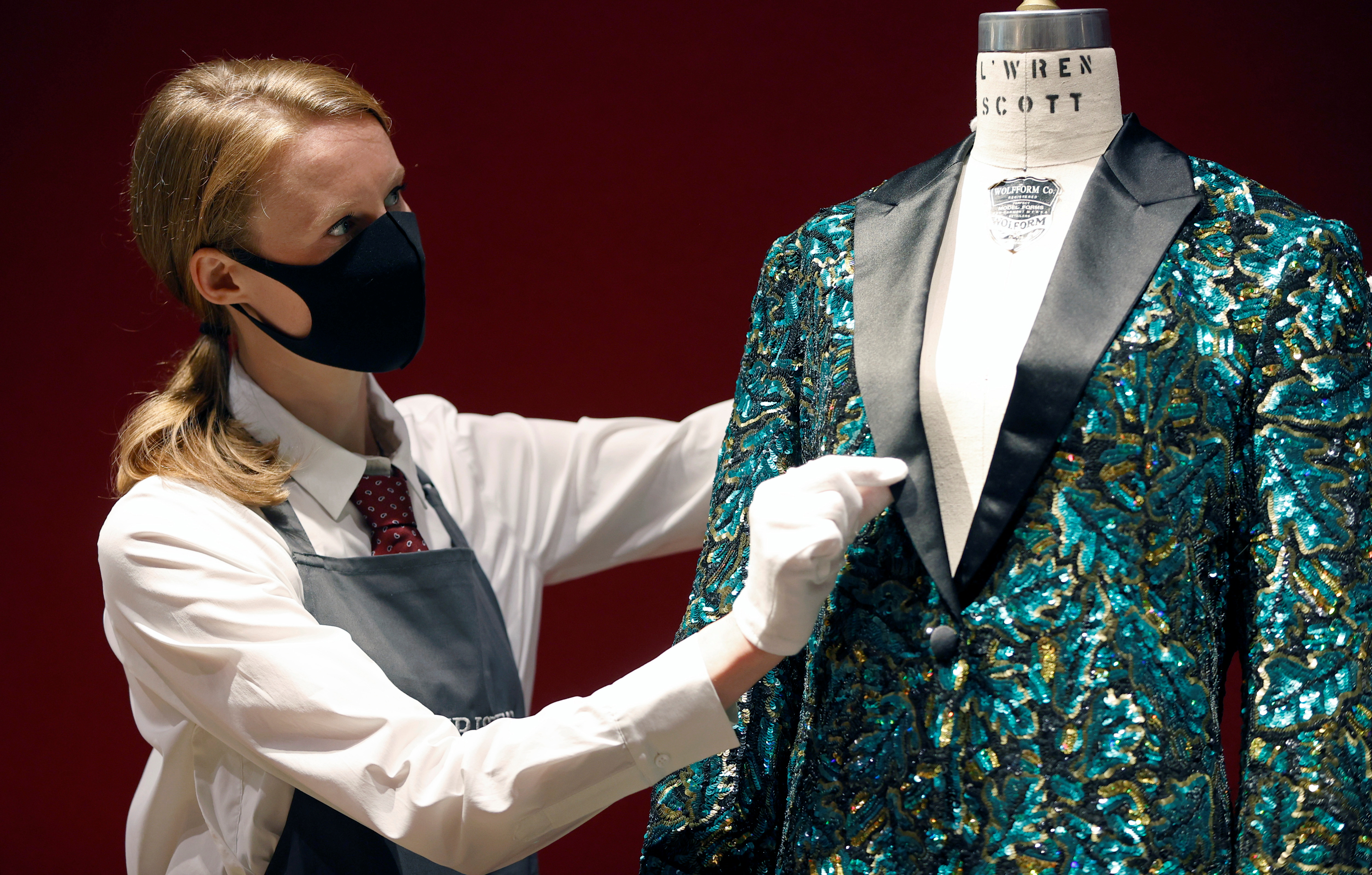 A gallery assistant poses for a photograph next to the Oak Leaf 'Glamouflage' jacket designed for Mick Jagger by designer L'Wren Scott at Christie's in London, Britain, June 10, 2021. REUTERS/John Sibley