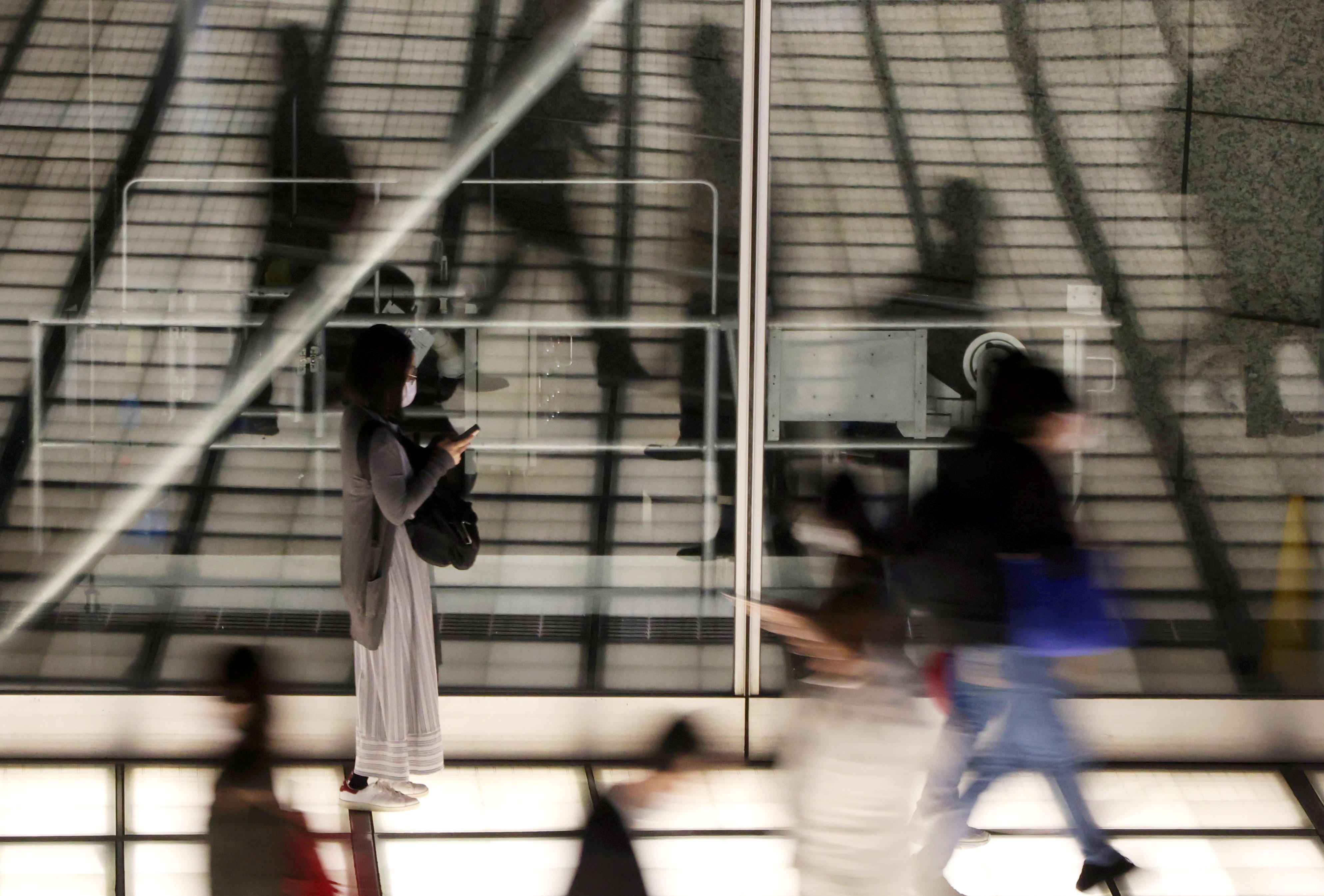 Passersby wearing protective face mask walk past a concourse amid the coronavirus disease (COVID-19) outbreak in Tokyo, Japan April 16, 2021. Picture taken by slow shutter speed.  REUTERS/Stringer