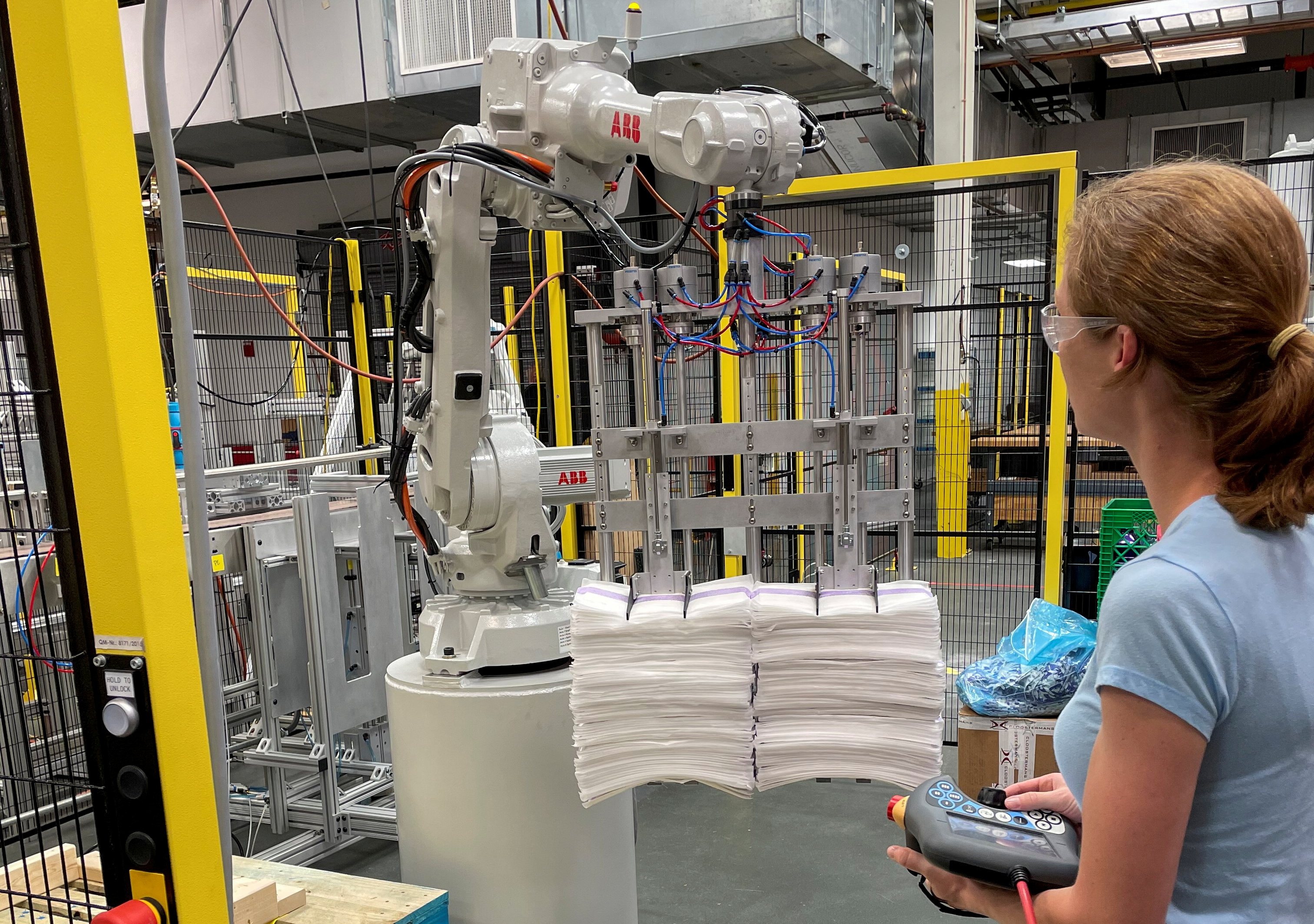 A researcher at Procter & Gamble's CoRE Fabric and Home Care Robotics Laboratory works on a new robot for handling sheets used in the company's floor care products, in Cincinnati, Ohio, U.S., May 27, 2021. REUTERS/Timothy Aeppel/File Photo