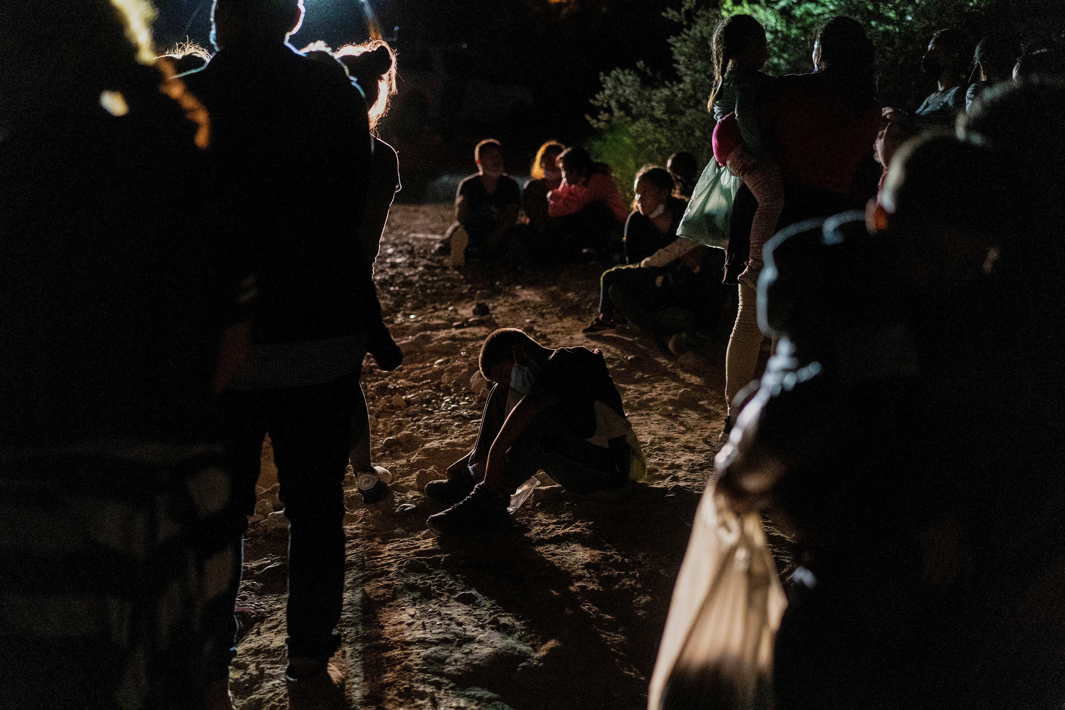 Asylum-seeking migrant families from Central America wait to be processed by the U.S. Border Patrol agents after crossing the Rio Grande river into the United States of America from Mexico in Roma, Texas, U.S., July 28, 2021. REUTERS/Go Nakamura