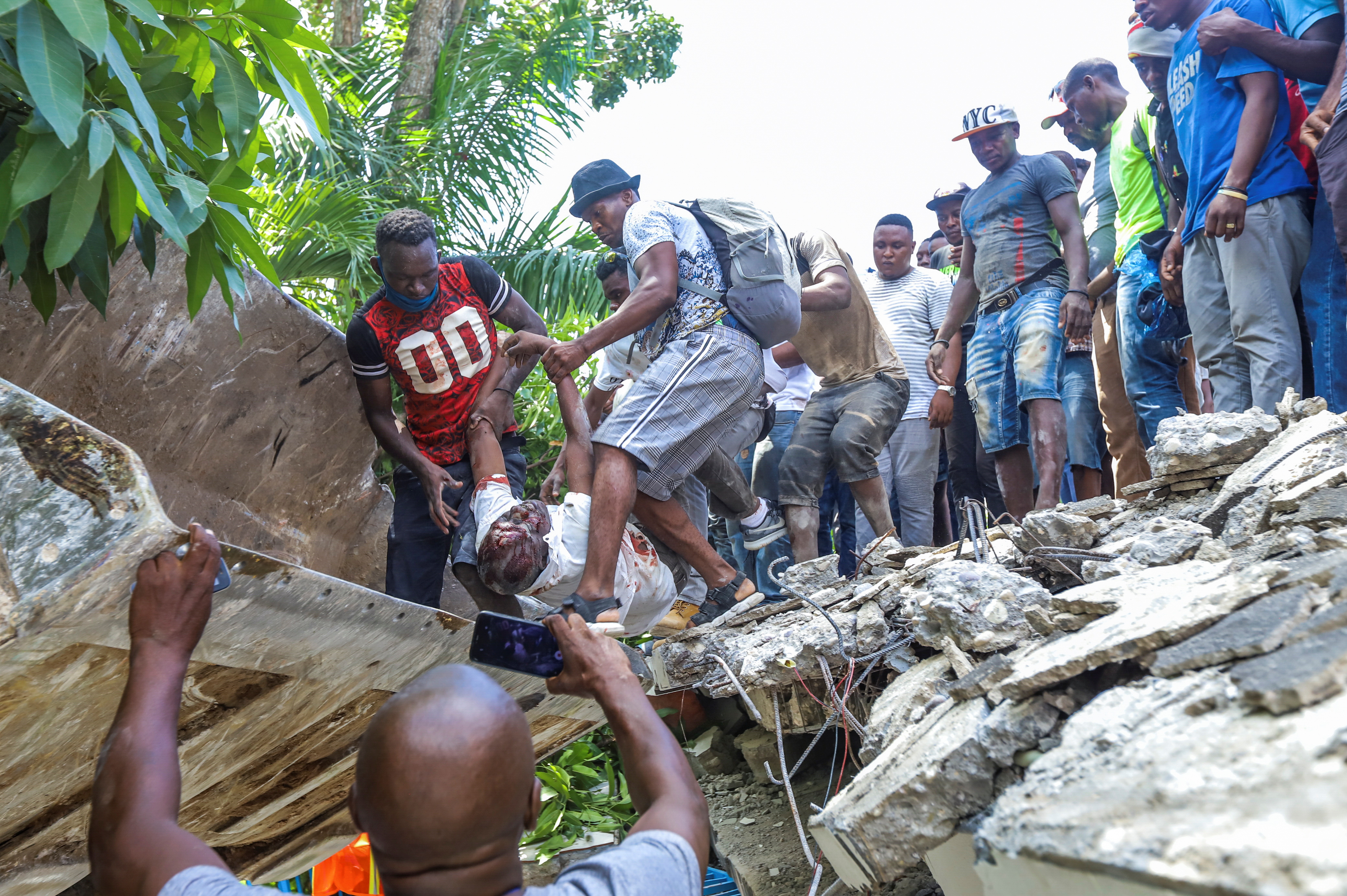 SENSITIVE MATERIAL. THIS IMAGE MAY OFFEND OR DISTURB People recover the body of politician Jean Gabriel Fortune from the rubble of a hotel following a 7.2 magnitude earthquake in Les Cayes, Haiti August 14, 2021. REUTERS/Ralph Tedy Erol NO RESALES. NO ARCHIVES