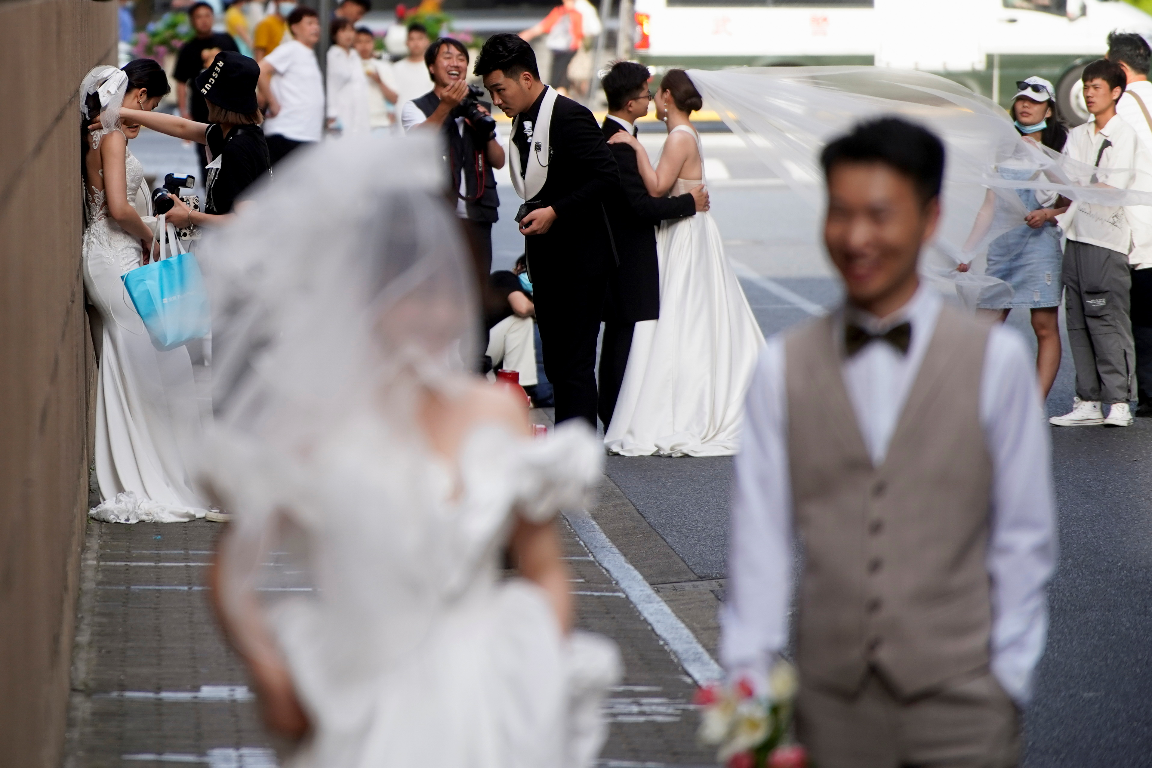 Couples prepare to get their photo taken during a wedding photography shoot on a street, amid the coronavirus disease (COVID-19) pandemic, in Shanghai, China May 31, 2021. REUTERS/Aly Song
