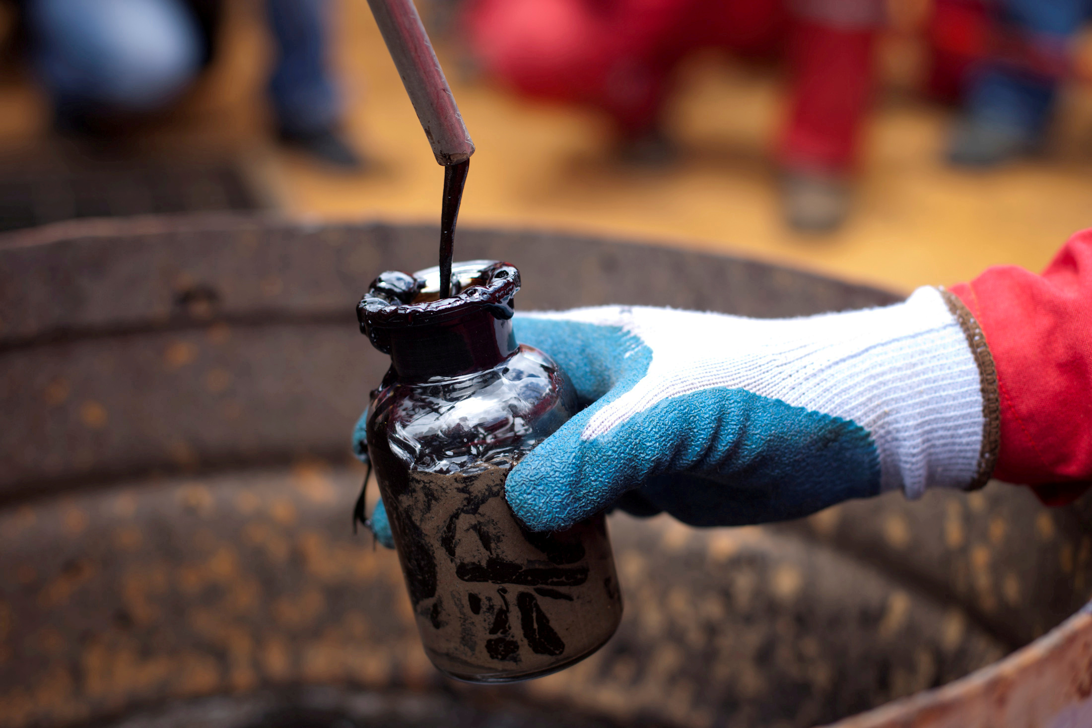 A worker collects a crude oil sample at an oil well operated by Venezuela