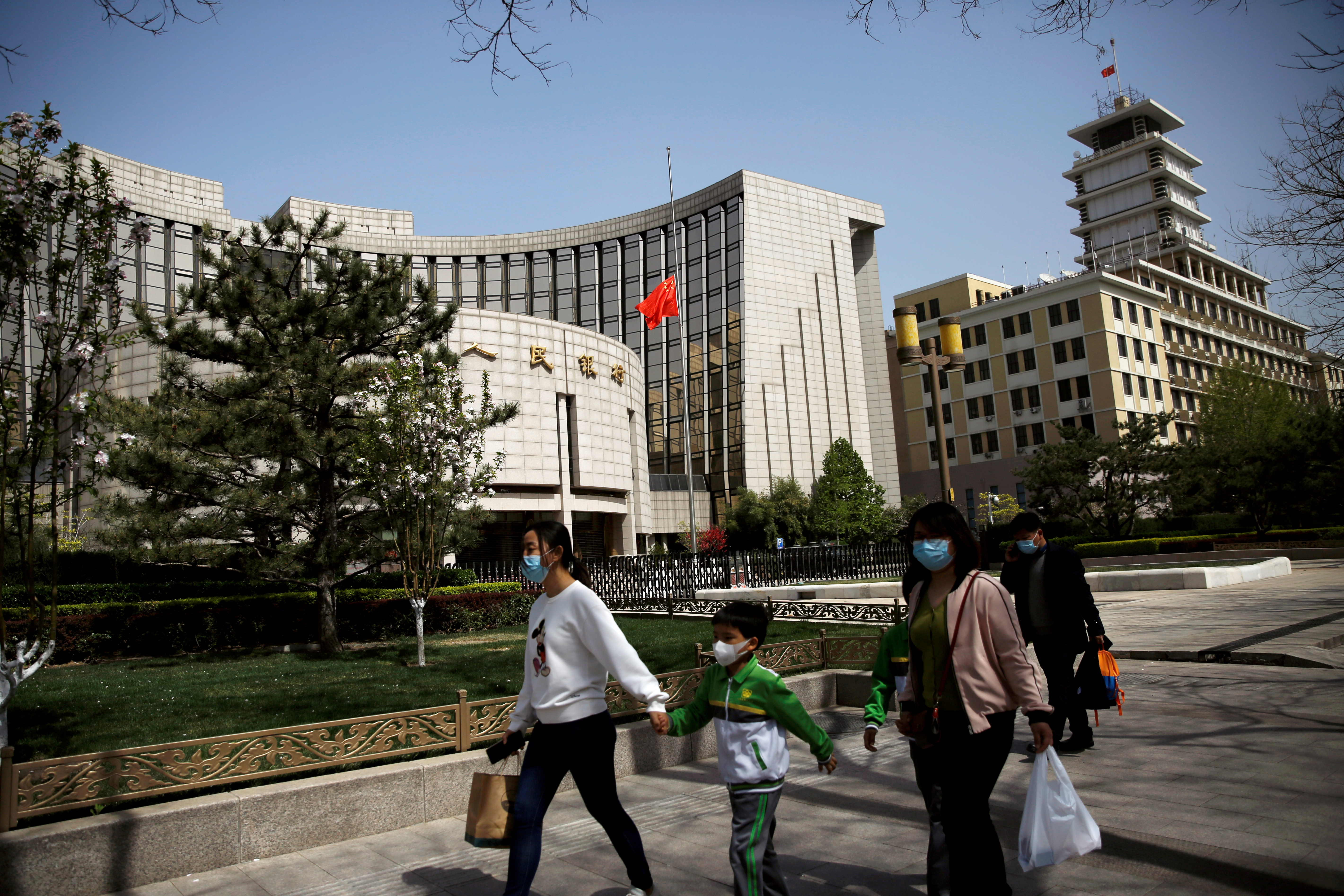 People wearing face masks walk past the headquarters of Chinese central bank People's Bank of China (PBOC), April 4, 2020. REUTERS/Tingshu Wang