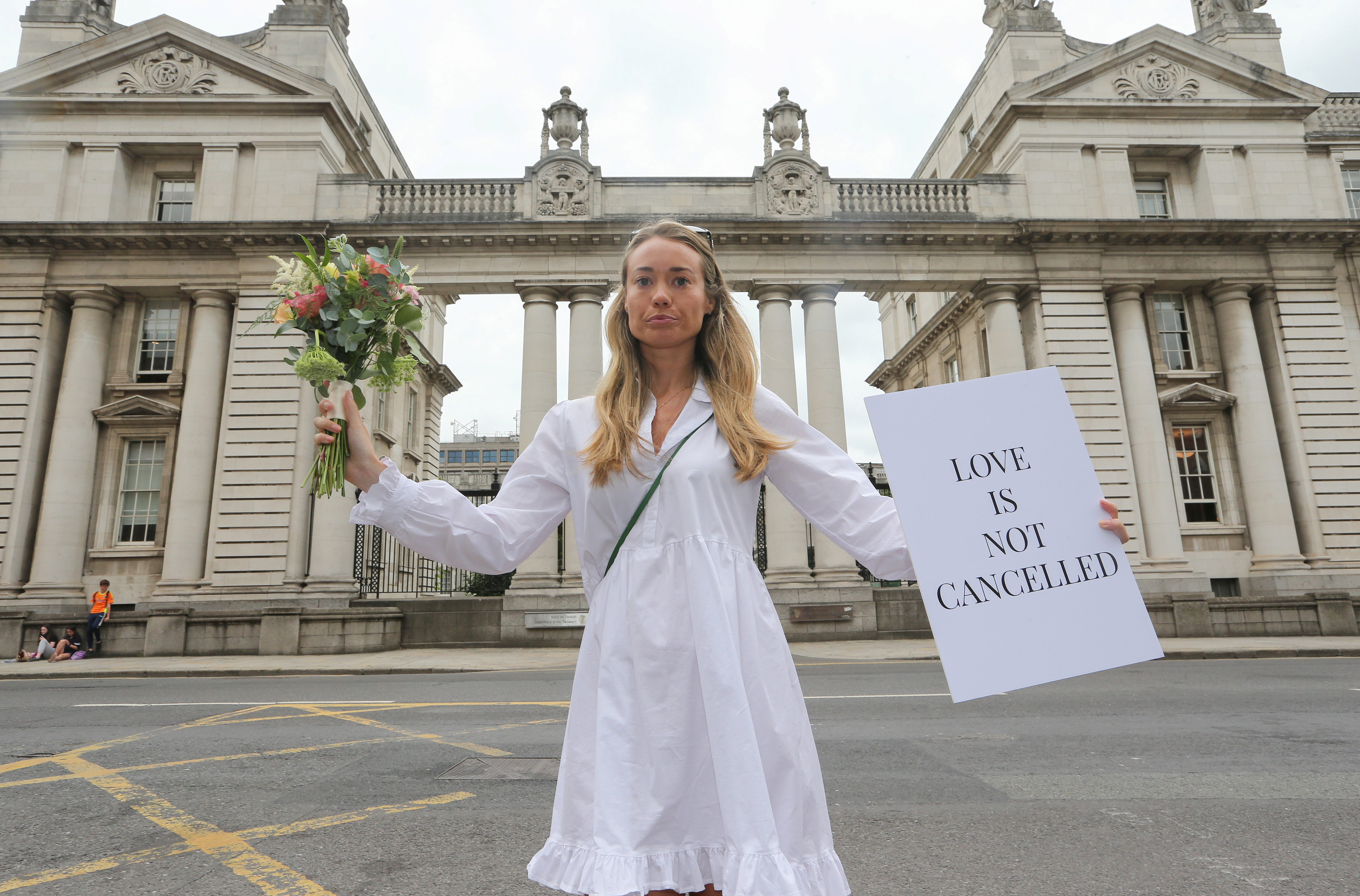 Orla O'Huadaigh holds up a sign at a protest march to Government Buildings in a bid to allow up to 100 guests to attend weddings this year in Dublin, Ireland, July 27, 2021. REUTERS/Lorraine O'Sullivan