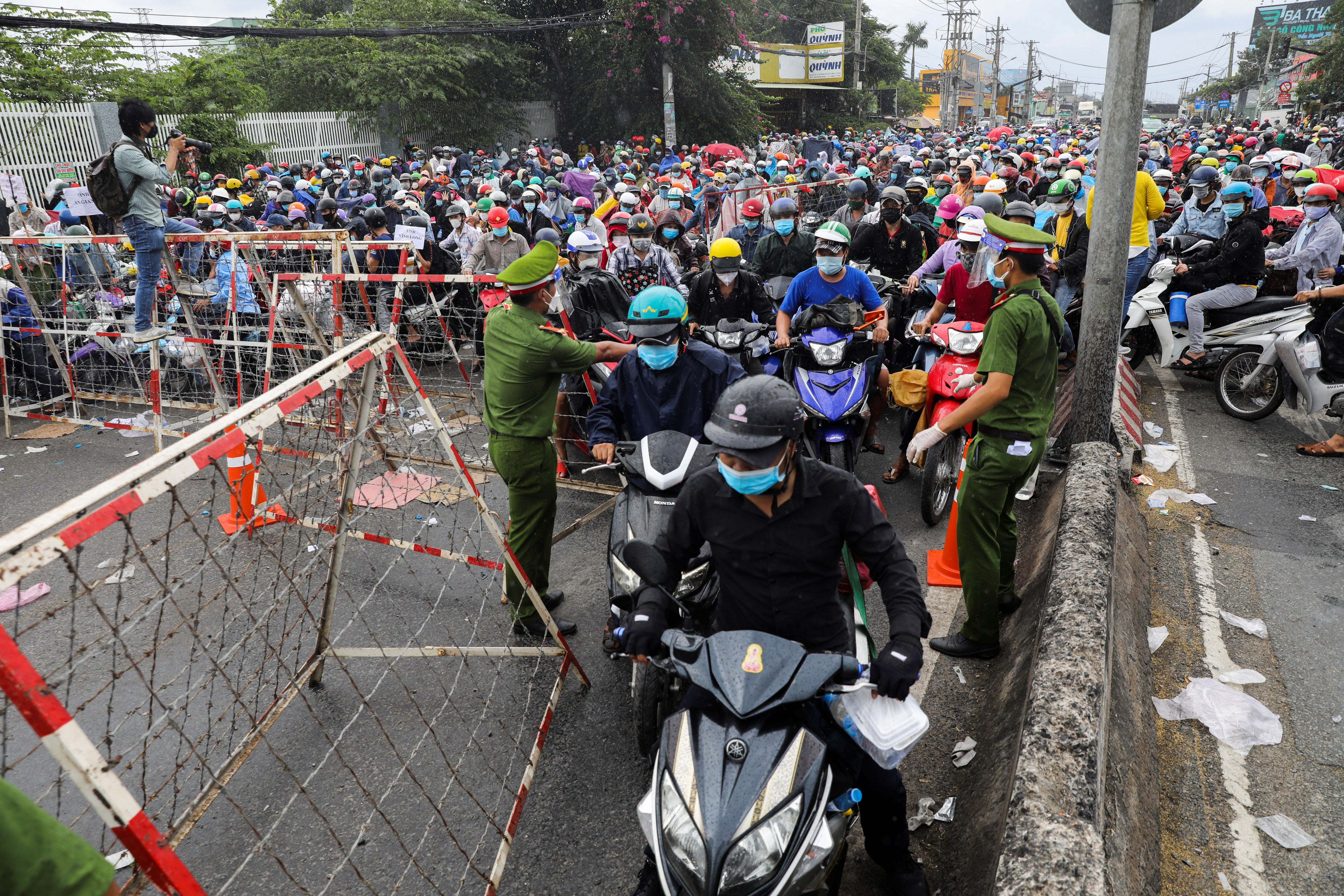 People, mostly migrant workers who are planning to return to their hometowns, wait at a checkpoint to leave Ho Chi Minh City, Vietnam October 1, 2021.  REUTERS/Stringer