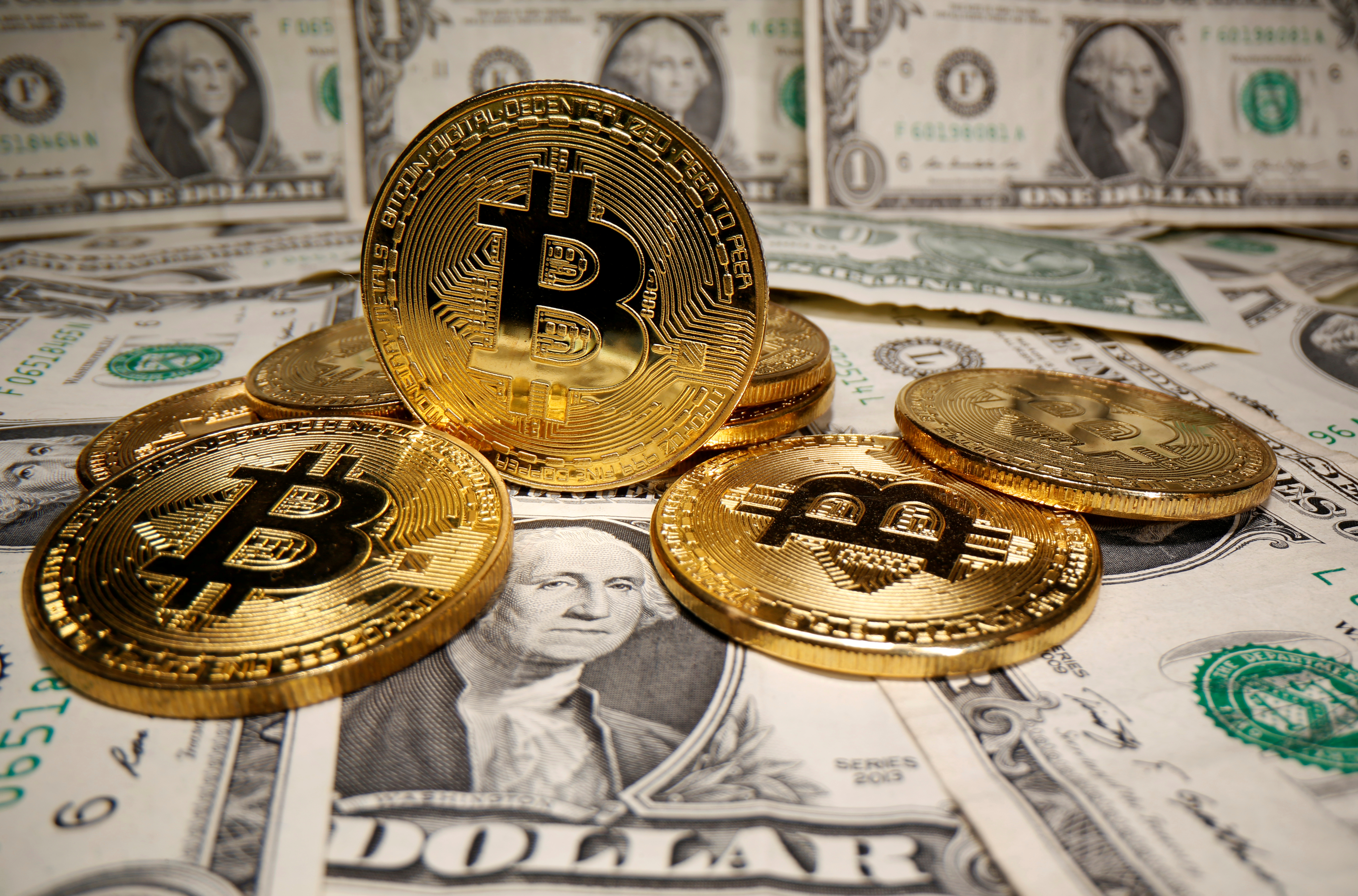 Representations of virtual currency Bitcoin are placed on U.S. Dollar banknotes in this illustration taken May 26, 2020. REUTERS/Dado Ruvic/Illustration/File Photo