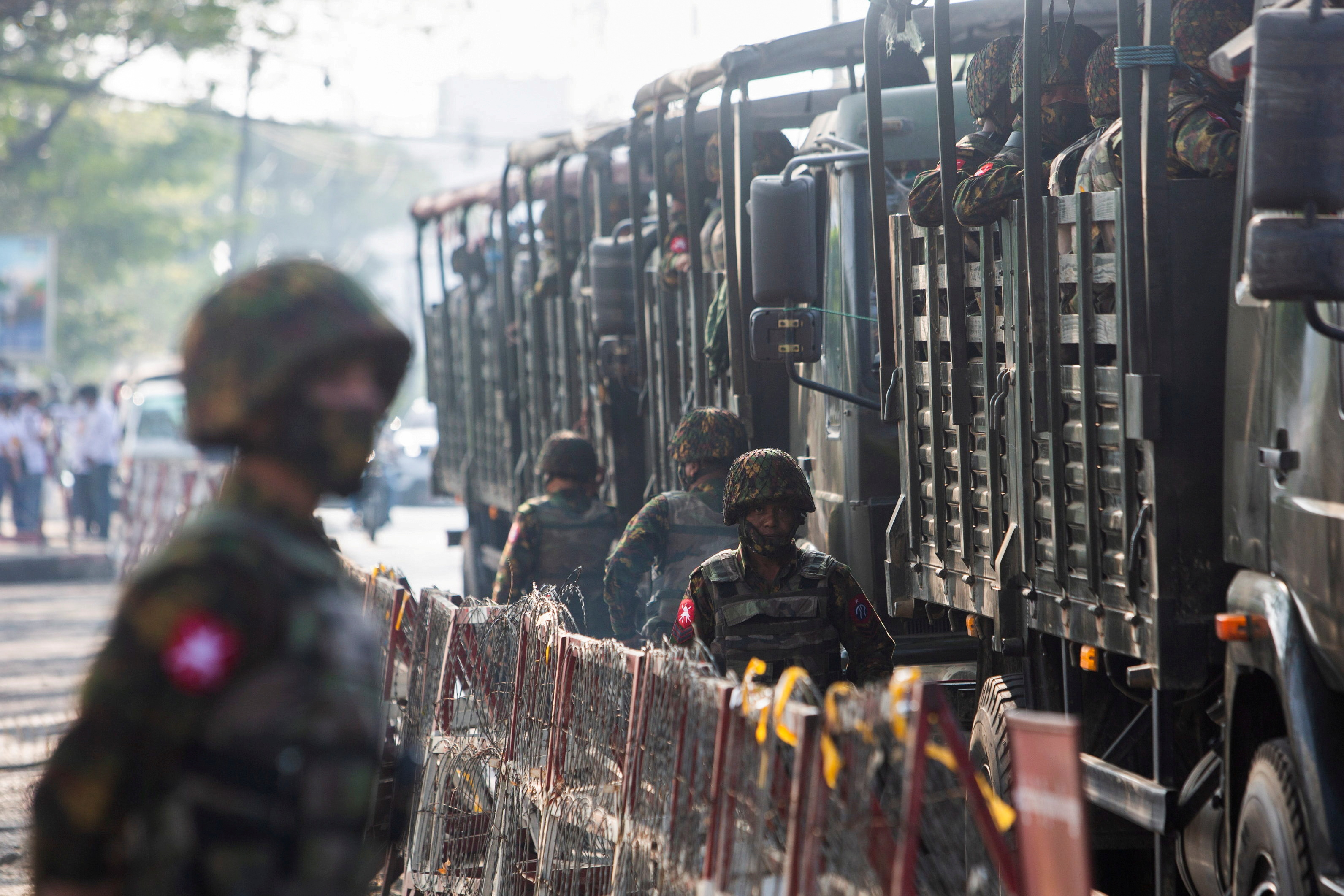 Soldiers stand next to military vehicles as people gather to protest against the military coup, in Yangon, Myanmar, February 15, 2021. REUTERS/Stringer/File Photo