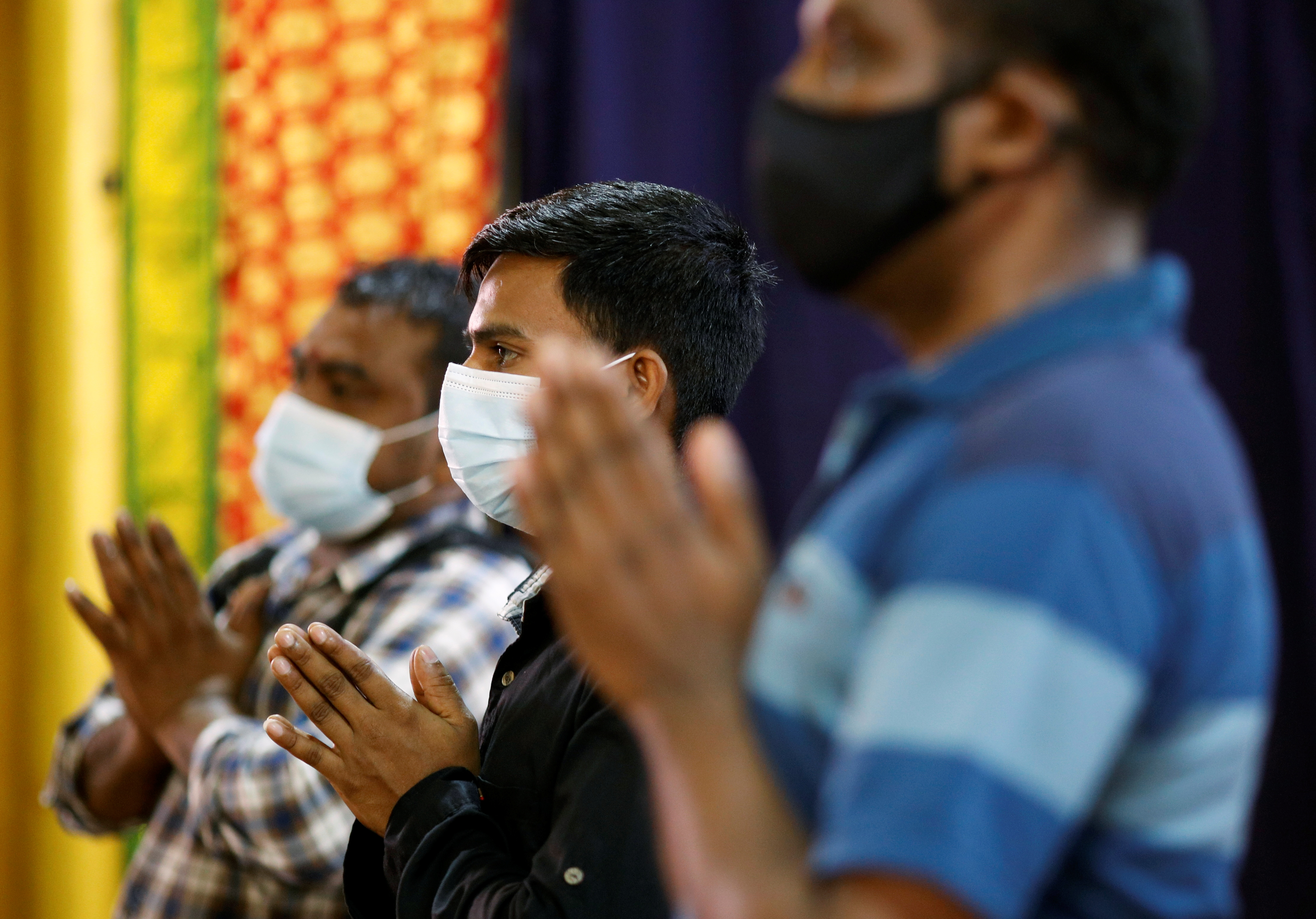 Migrant workers pray at a temple, before enjoying time off at Little India, as part of a pilot programme to allow fully vaccinated migrant workers back to the community after more than a year of movement curbs due to the coronavirus disease (COVID-19) outbreak, in Singapore September 15, 2021. REUTERS/Edgar Su