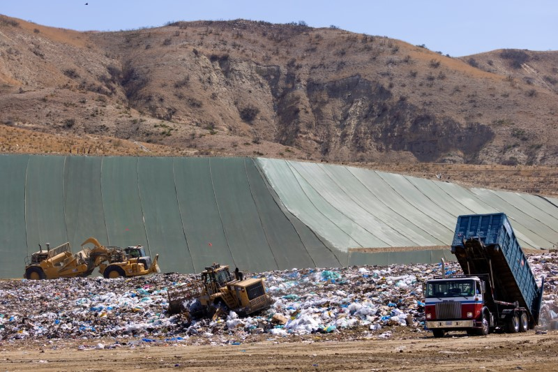 Workers use heavy machinery to move trash and waste at the Frank R. Bowerman landfill on Irvine, California, U.S., June 15, 2021. REUTERS/Mike Blake