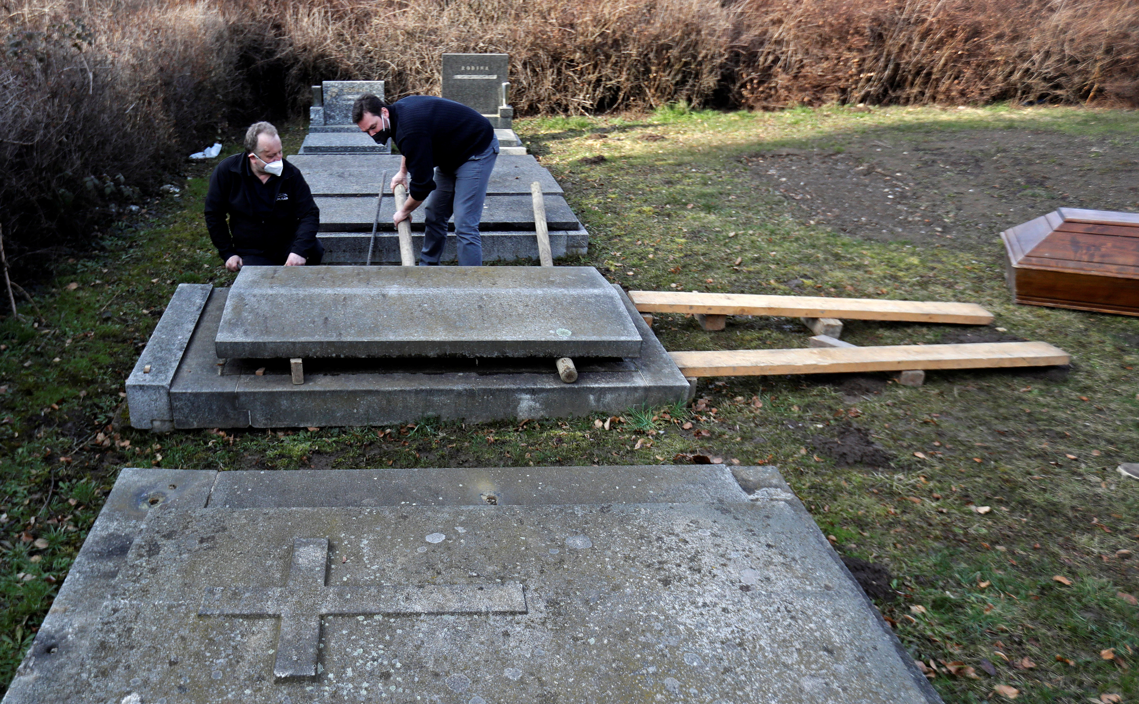 A grave digging instructor looks at an actor Tomas Novotny (R) opening an empty grave at a training cemetery as a part of Novotny's re-qualification procedure amid the coronavirus disease (COVID-19) outbreak in Prague, Czech Republic, March 9, 2021.  REUTERS/David W Cerny