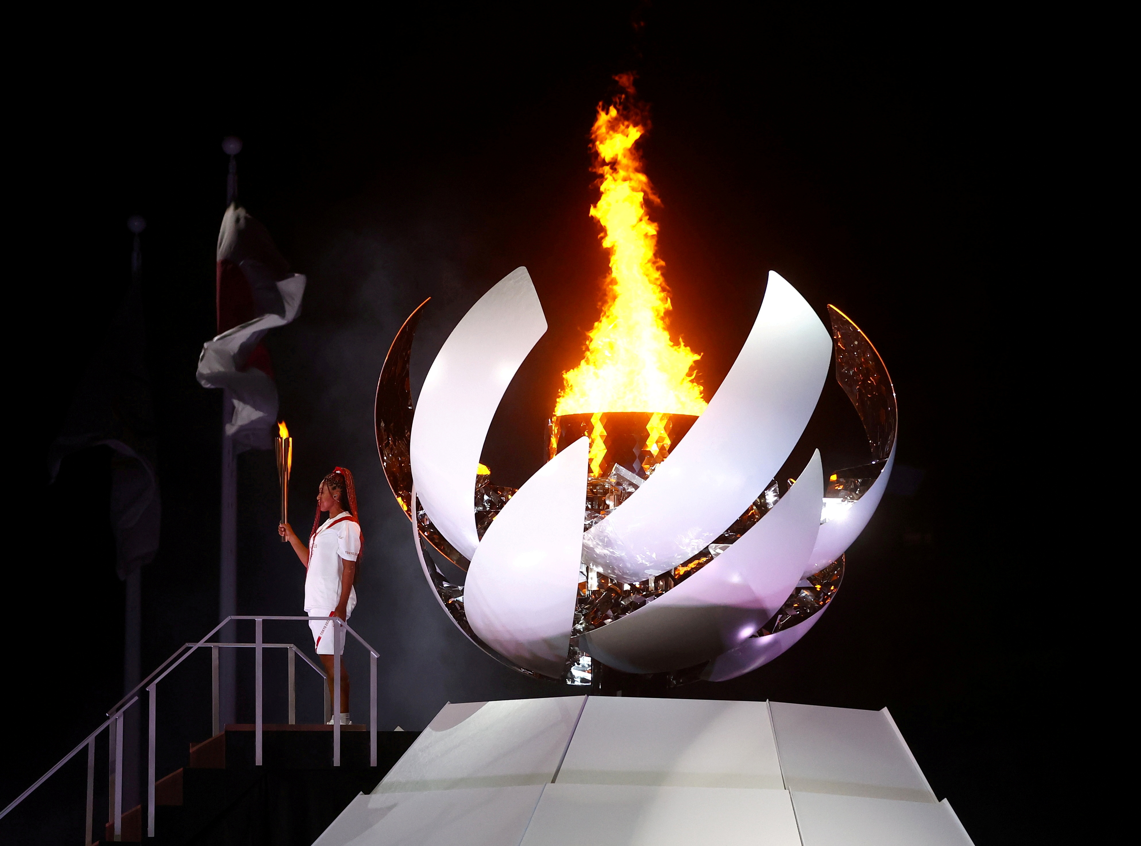 Naomi Osaka of Japan holds the Olympic torch after lighting the cauldron at the Tokyo 2020 Olympics opening ceremony, July 23, 2021. REUTERS/Kai Pfaffenbach
