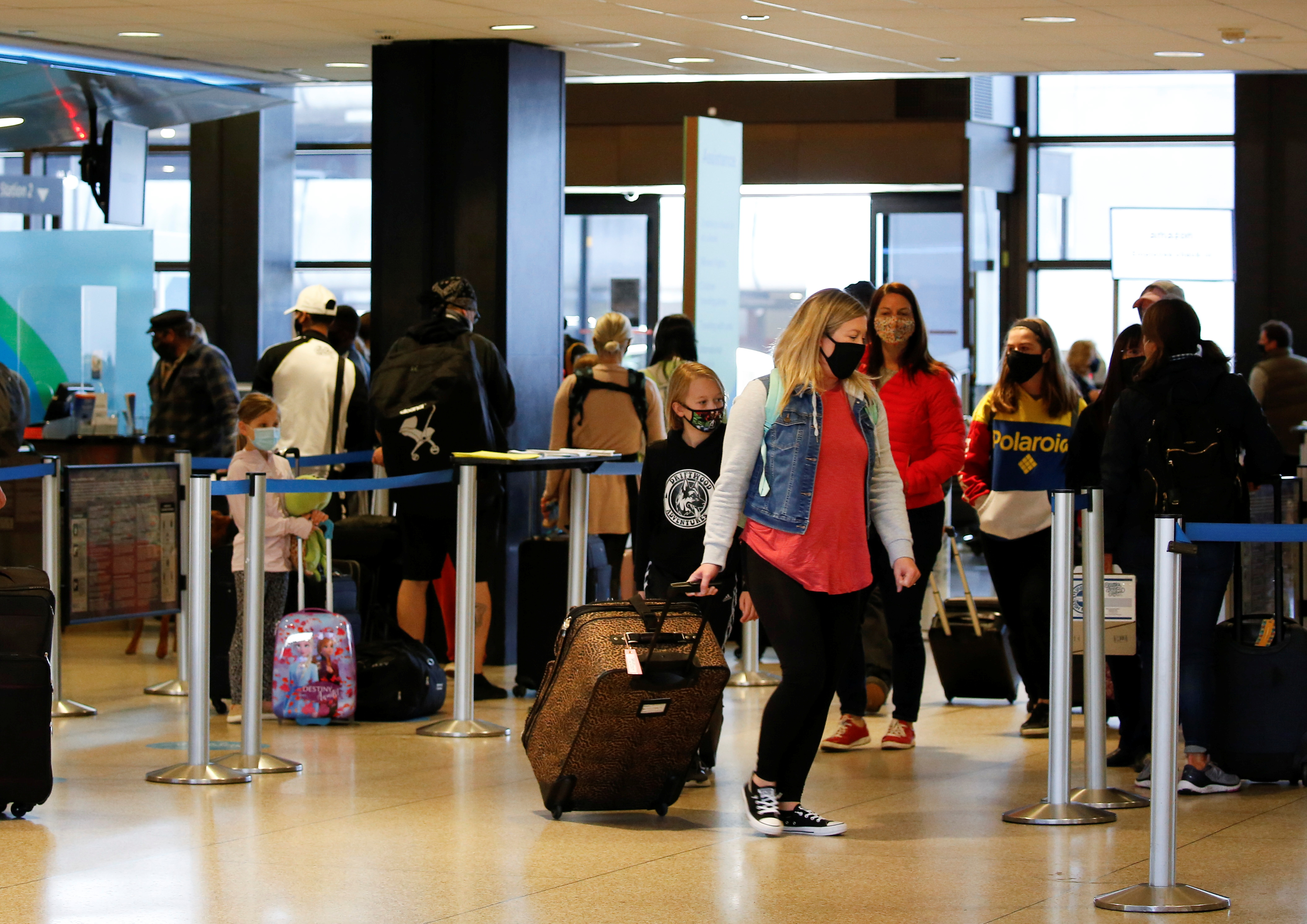 Travelers stand at check-in lines at Seattle-Tacoma International Airport in SeaTac, Washington, U.S. April 12, 2021.  REUTERS/Lindsey Wasson
