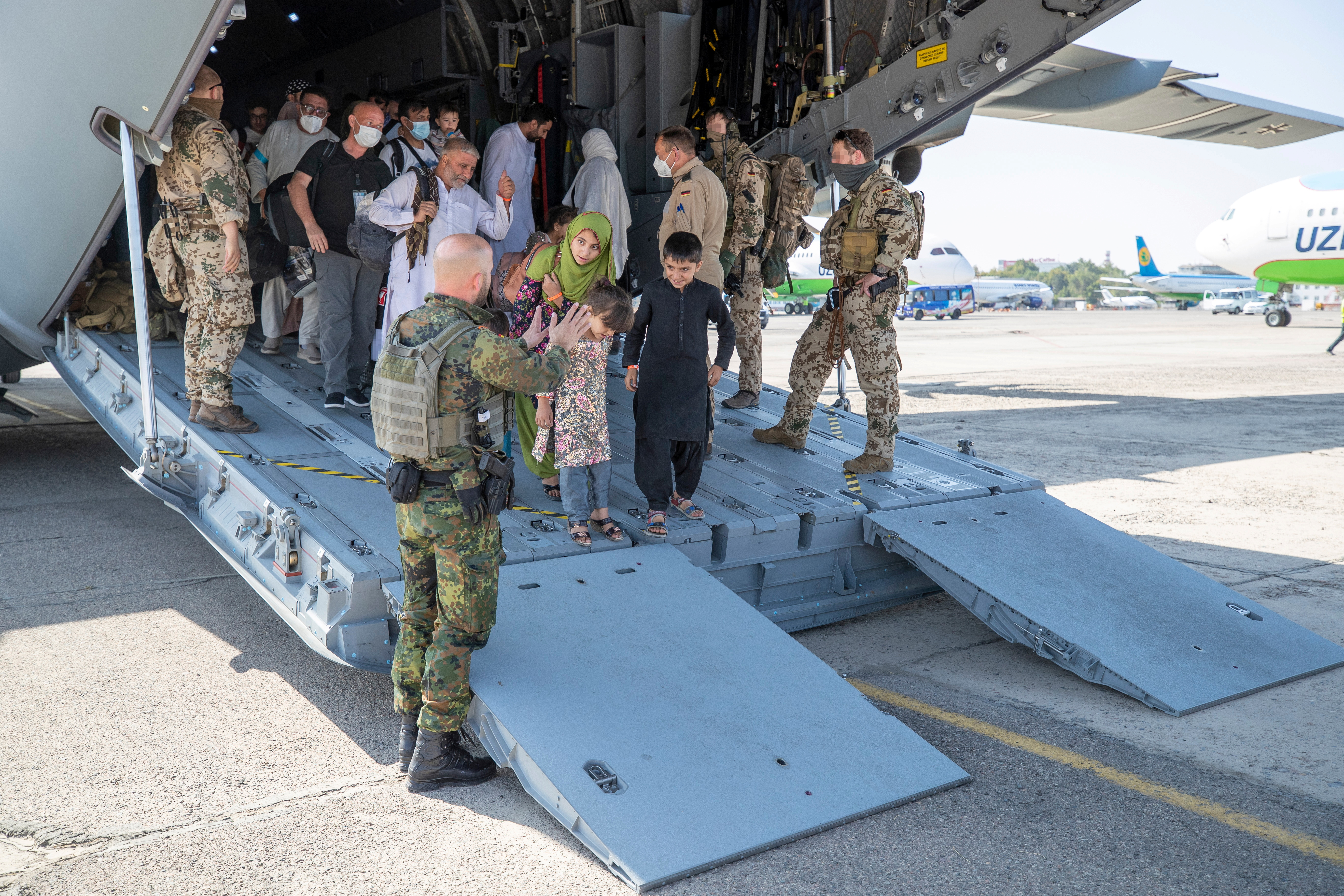 A handout photo obtained from the Bundeswehr Twitter account @Bw_Einsatz on August 18, 2021 shows staff talking to evacuees from Afghanistan as they arrive in an Airbus A400 transport aircraft of the German Air Force Luftwaffe in Tashkent, Uzbekistan. Marc Tessensohn/Twitter @Bw_Einsatz/Handout via REUTERS    ATTENTION EDITORS - THIS IMAGE HAS BEEN SUPPLIED BY A THIRD PARTY.   NO RESALES. NO ARCHIVES. PARTS OF THE IMAGE HAVE BEEN PIXELATED AT SOURCE.