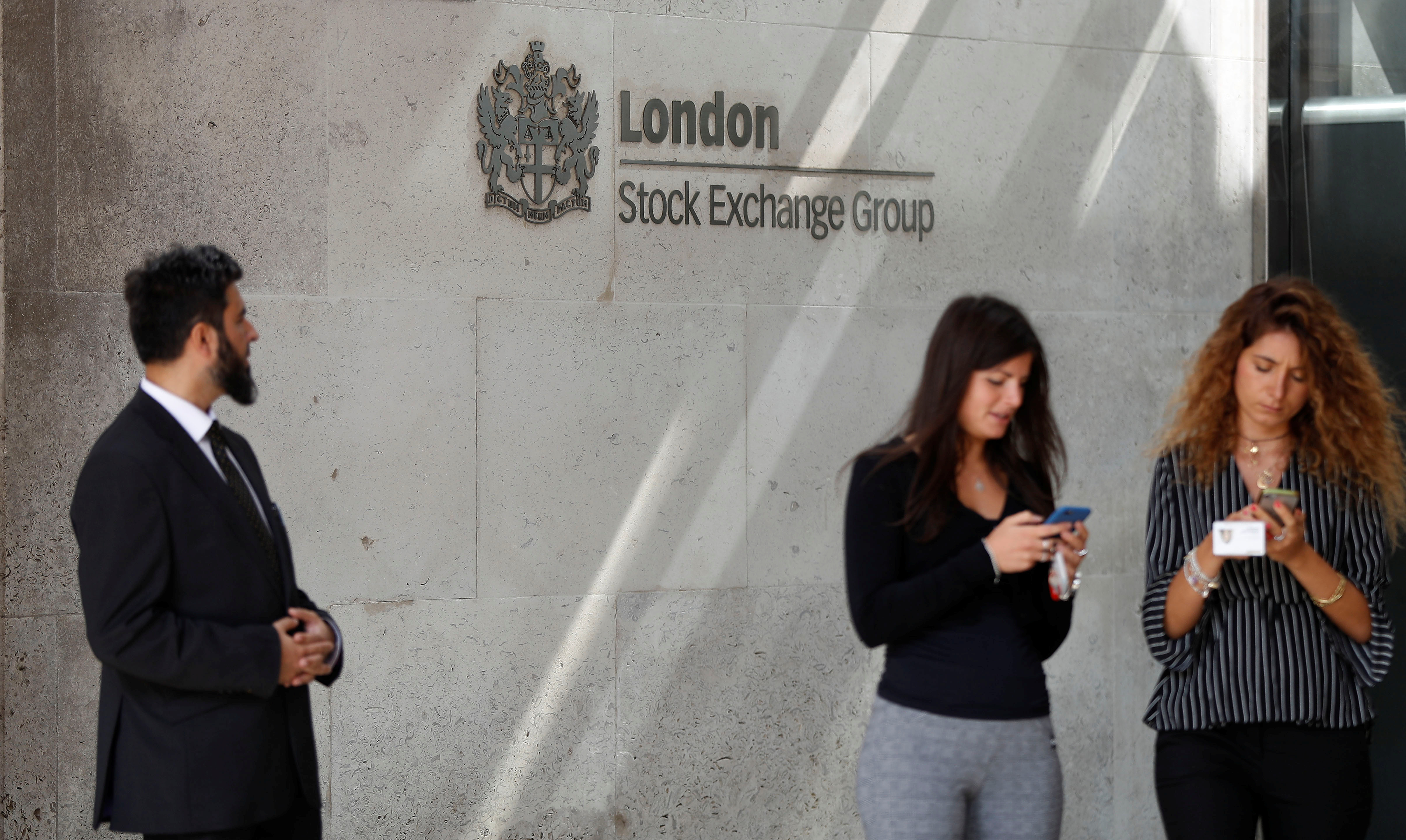 People check their mobile phones as they stand outside the entrance of the London Stock Exchange in London, Britain. Aug 23, 2018. REUTERS/Peter Nicholls