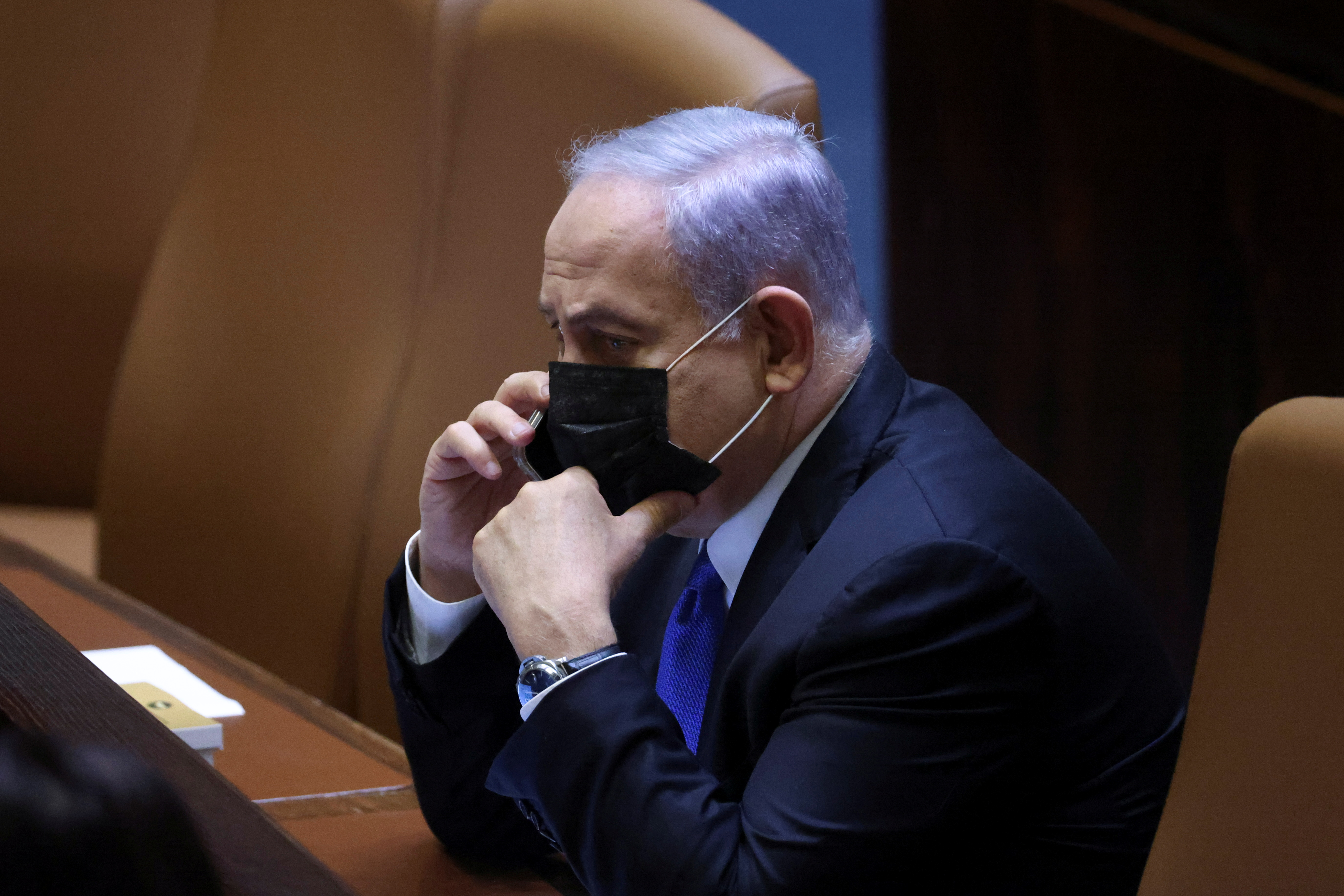 Israeli Prime Minister Benjamin Netanyahu speaks on his mobile phone during a special session of the Knesset whereby Israeli lawmakers elect a new president, at the plenum in the Knesset, Israel's parliament, in Jerusalem June 2, 2021. REUTERS/Ronen Zvulun