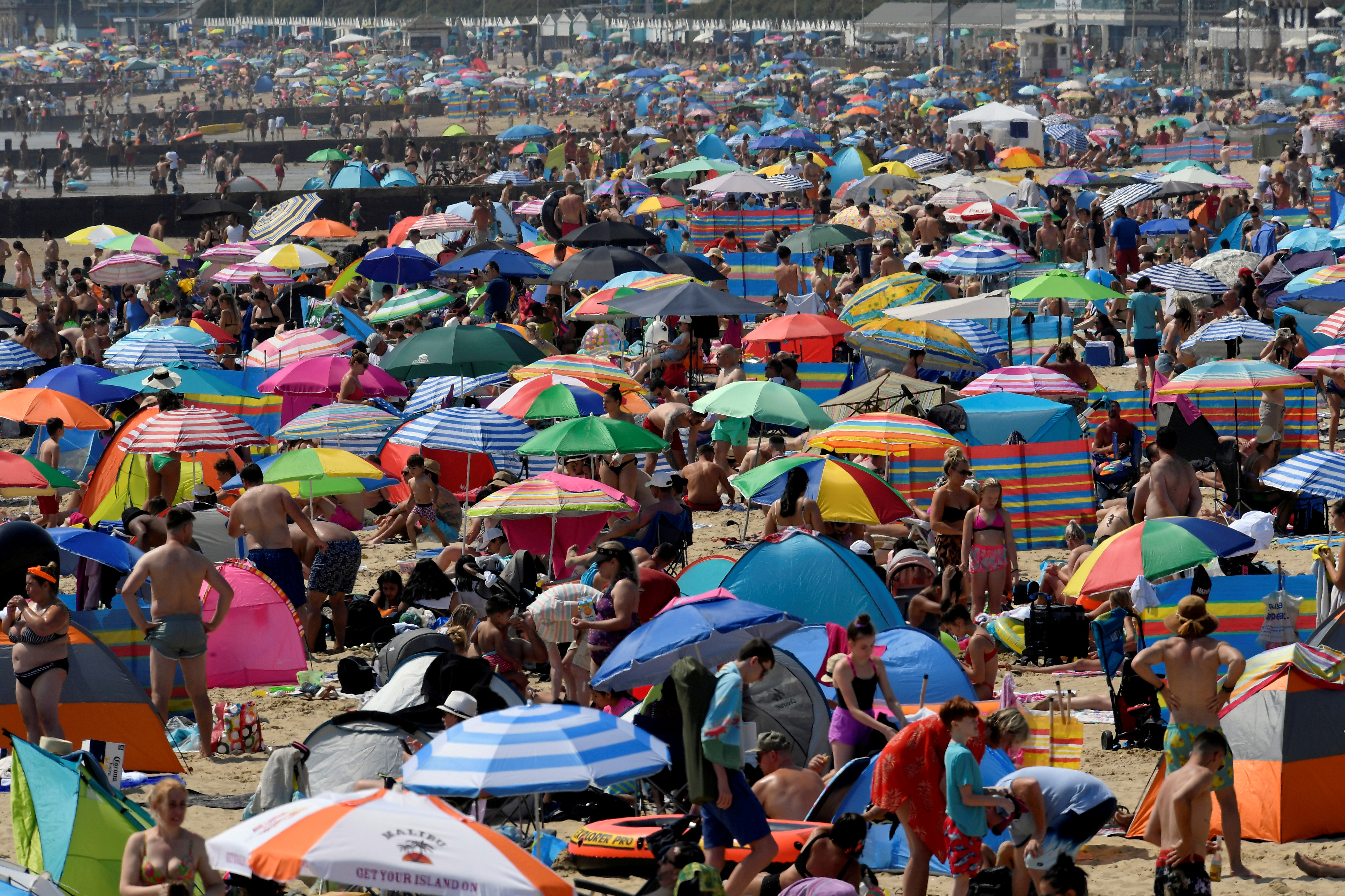 People enjoy the sunny weather at the Bournemouth Beach, amid the coronavirus disease (COVID-19) outbreak, in Bournemouth, Britain July 31, 2020. REUTERS/Toby Melville/File Photo