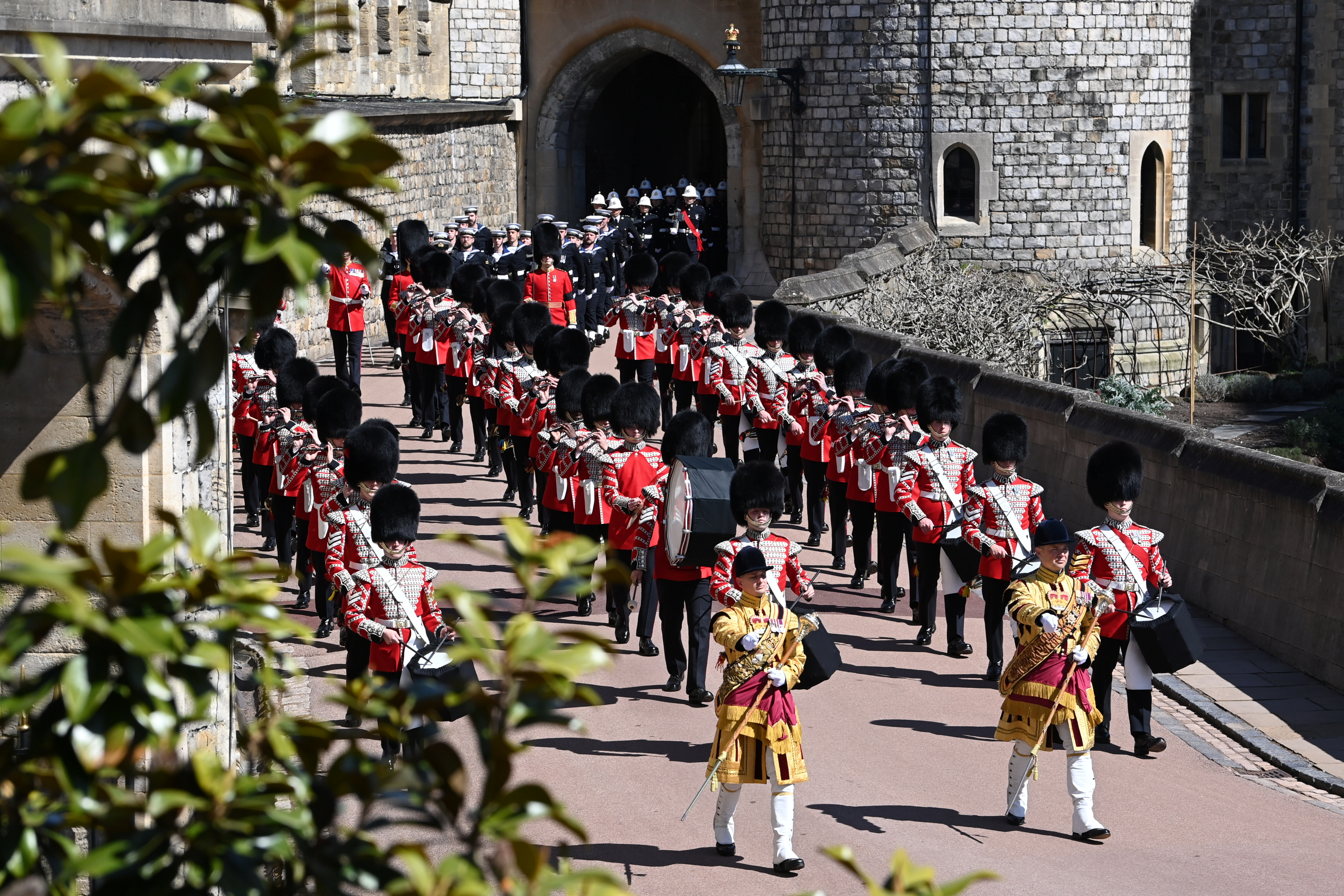 Members of the military march on the grounds of the Windsor Castle as the Royal Standard fag flutters on the day of the funeral of Britain's Prince Philip, husband of Queen Elizabeth, who died at the age of 99, at Windsor Castle in Windsor, Britain, April 17, 2021. Leon Neal/Pool via REUTERS