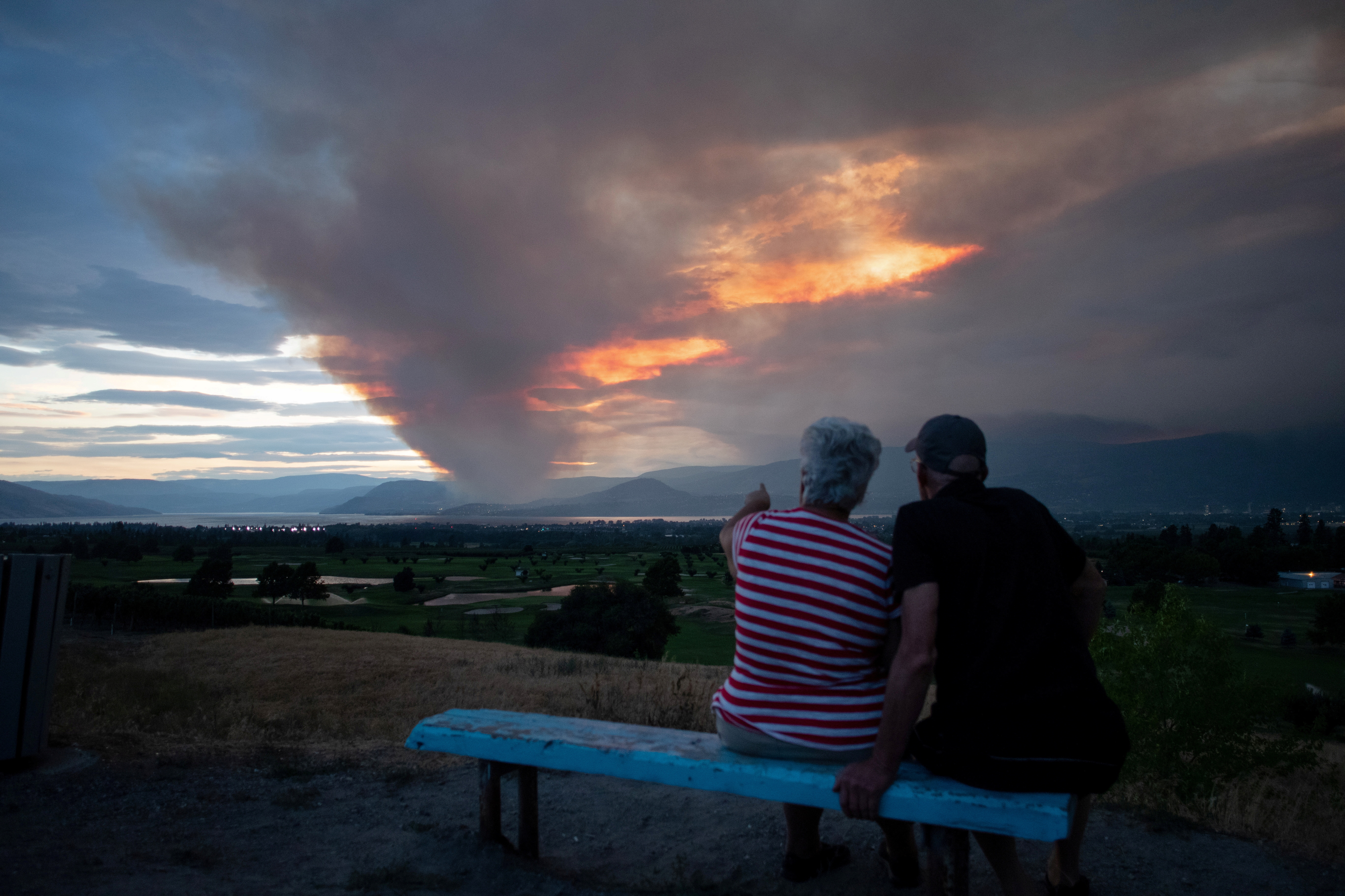 A couple view the newly ignited Mount Law wildfire, near Peachland and Glenrosa on the west side of Okanagan Lake, from the waterfront in Kelowna, British Columbia, Canada August 15, 2021. REUTERS/Artur Gajda