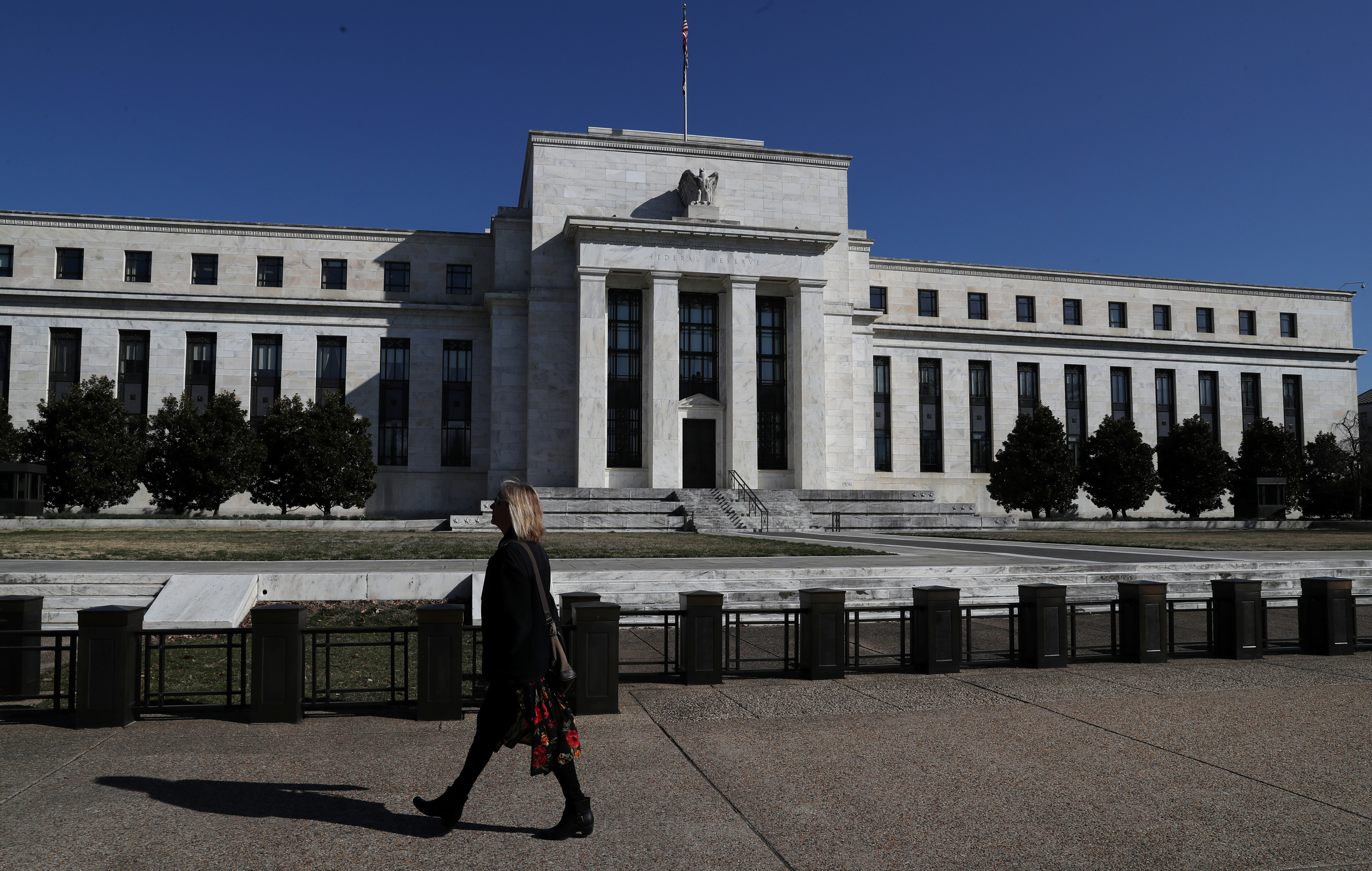 A pedestrian walks past the Federal Reserve Board building on Constitution Avenue in Washington, March 19, 2019. REUTERS/Leah Millis