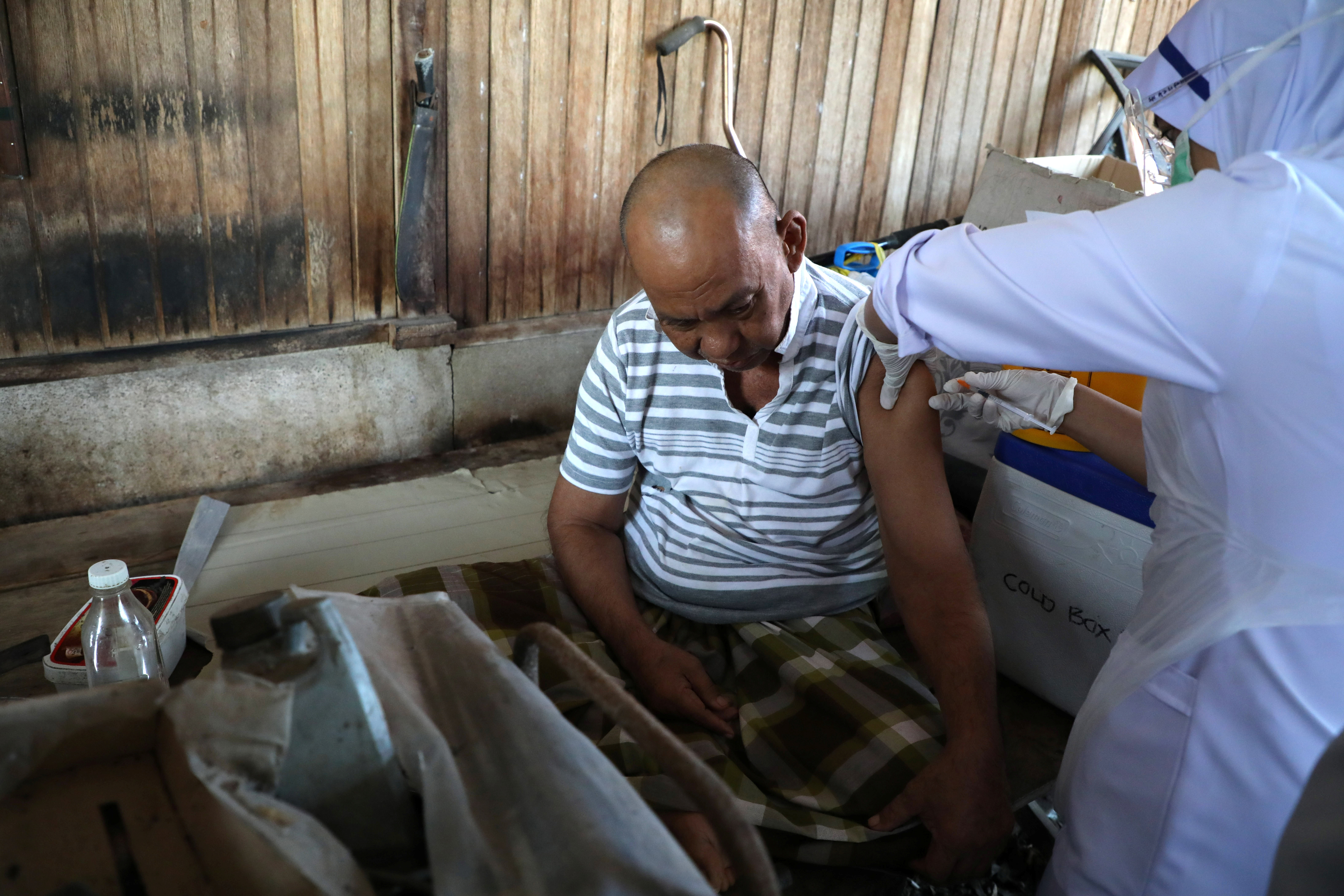 A healthcare worker administers the Pfizer coronavirus disease (COVID-19) vaccine to an elderly man at his home, in Kuala Langat, Malaysia July 17, 2021. REUTERS/Lim Huey Teng