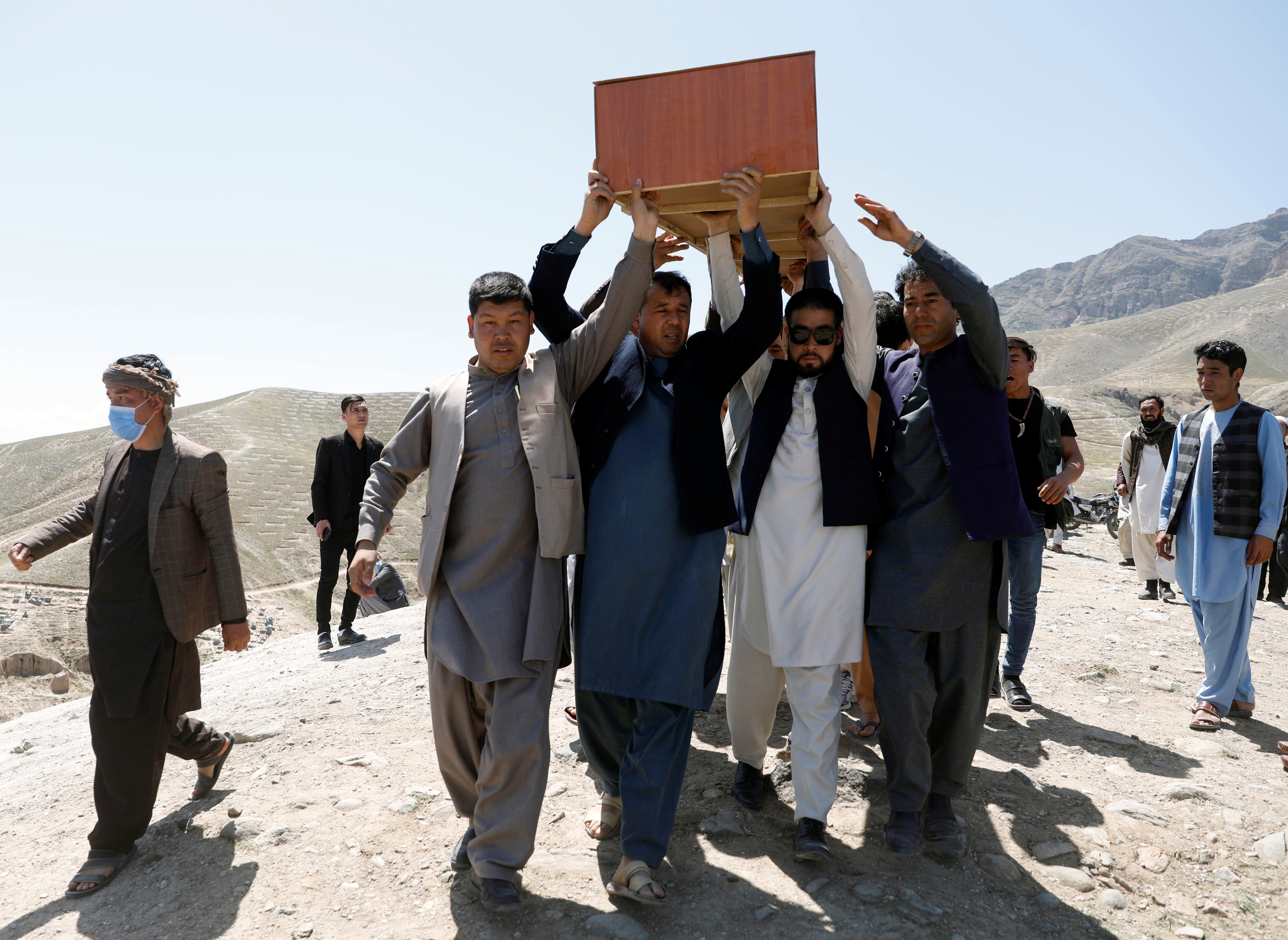 Afghan men carry the coffin of one of the victims of yesterday's explosion in Kabul, Afghanistan May 9, 2021. REUTERS/Stringer