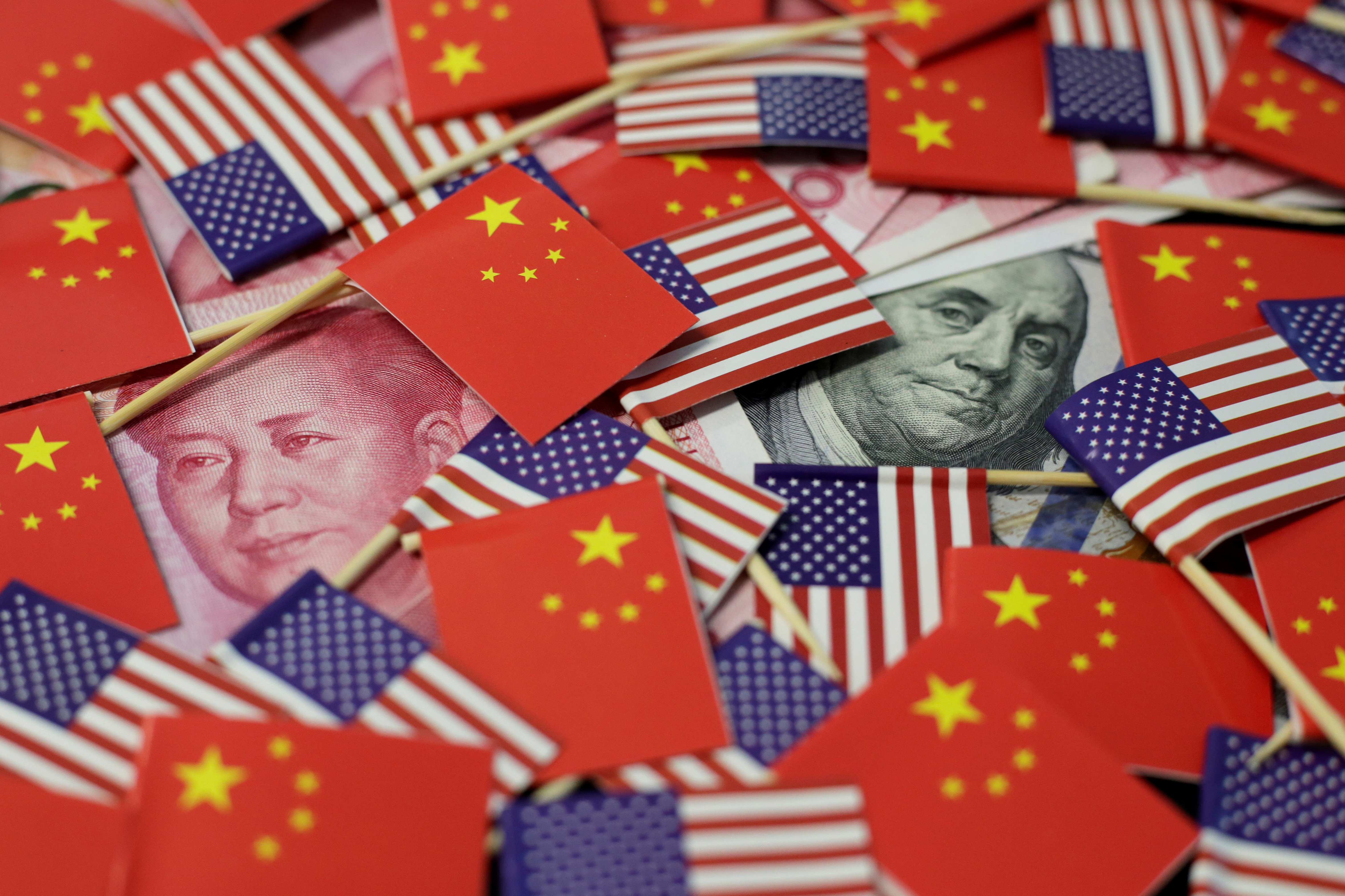 A U.S. dollar banknote featuring American founding father Benjamin Franklin and a China's yuan banknote featuring late Chinese chairman Mao Zedong are seen among U.S. and Chinese flags in this illustration picture taken May 20, 2019. REUTERS/Jason Lee/Illustration/File Photo