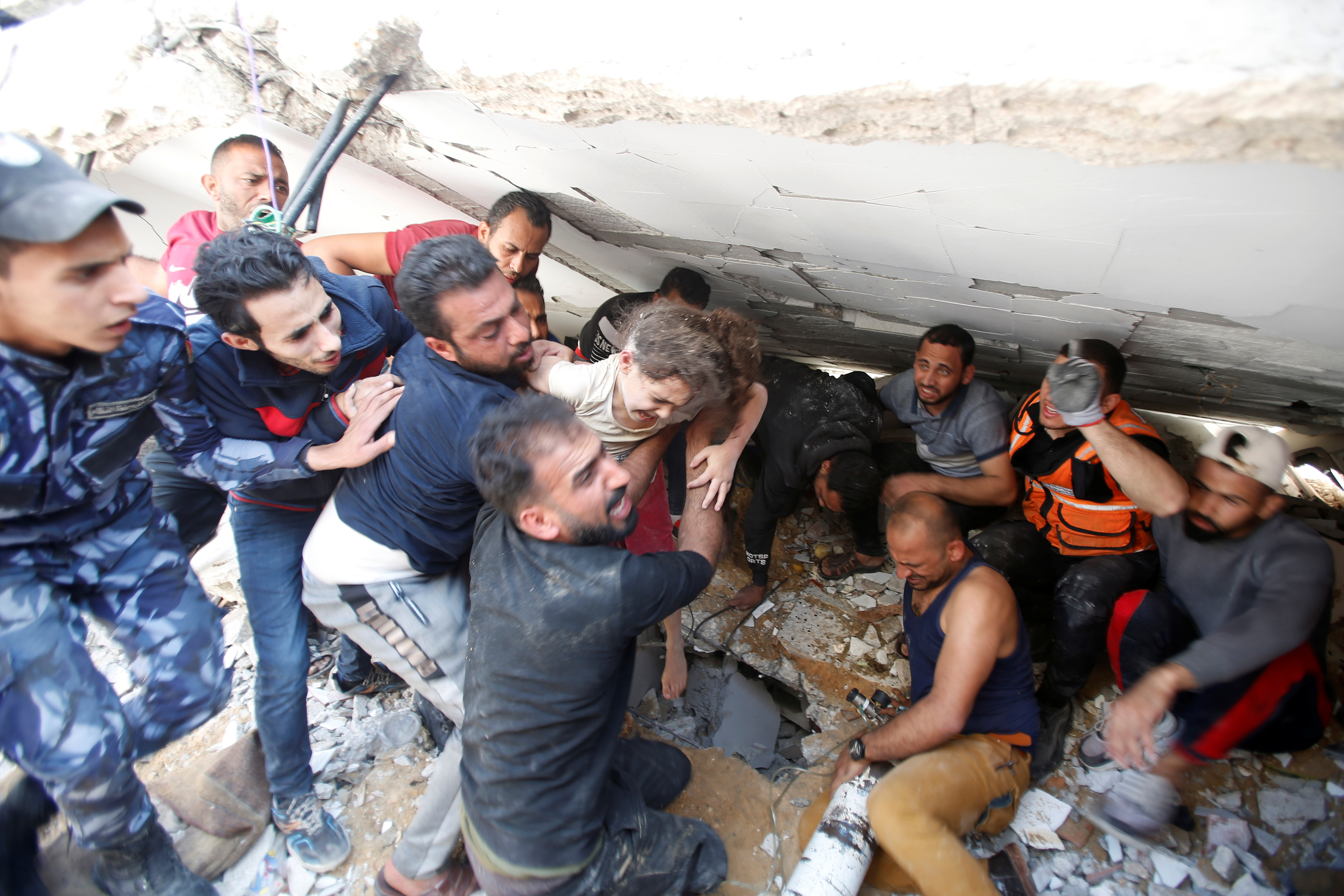 Rescuers carry Suzy Eshkuntana, 6, as they pull her from the rubble of a building at the site of Israeli air strikes, in Gaza City May 16, 2021. REUTERS/Mohammed Salem