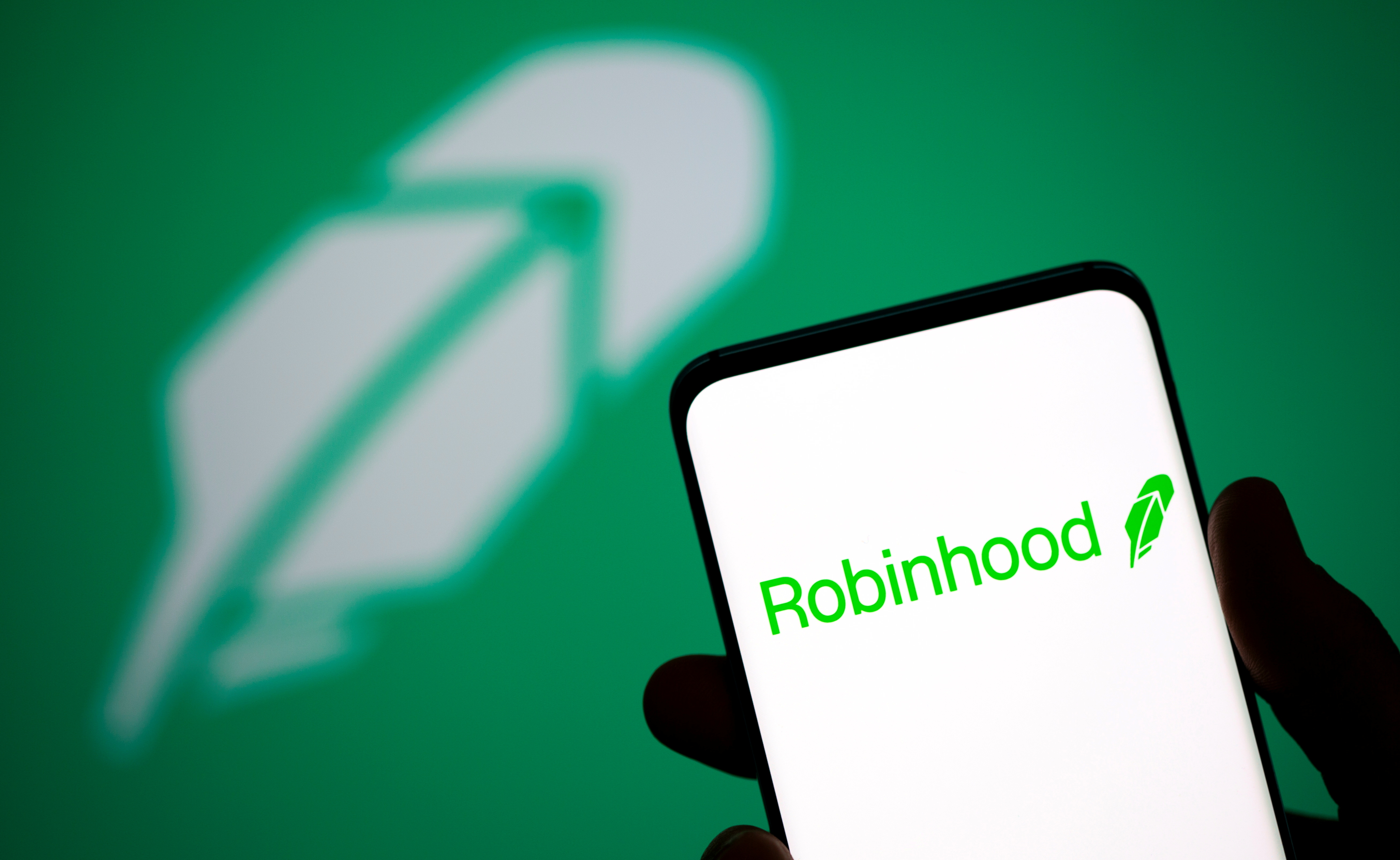Robinhood logo is seen on a smartphone in front of a displayed same logo in this illustration taken, July 2, 2021. REUTERS/Dado Ruvic/Illustration