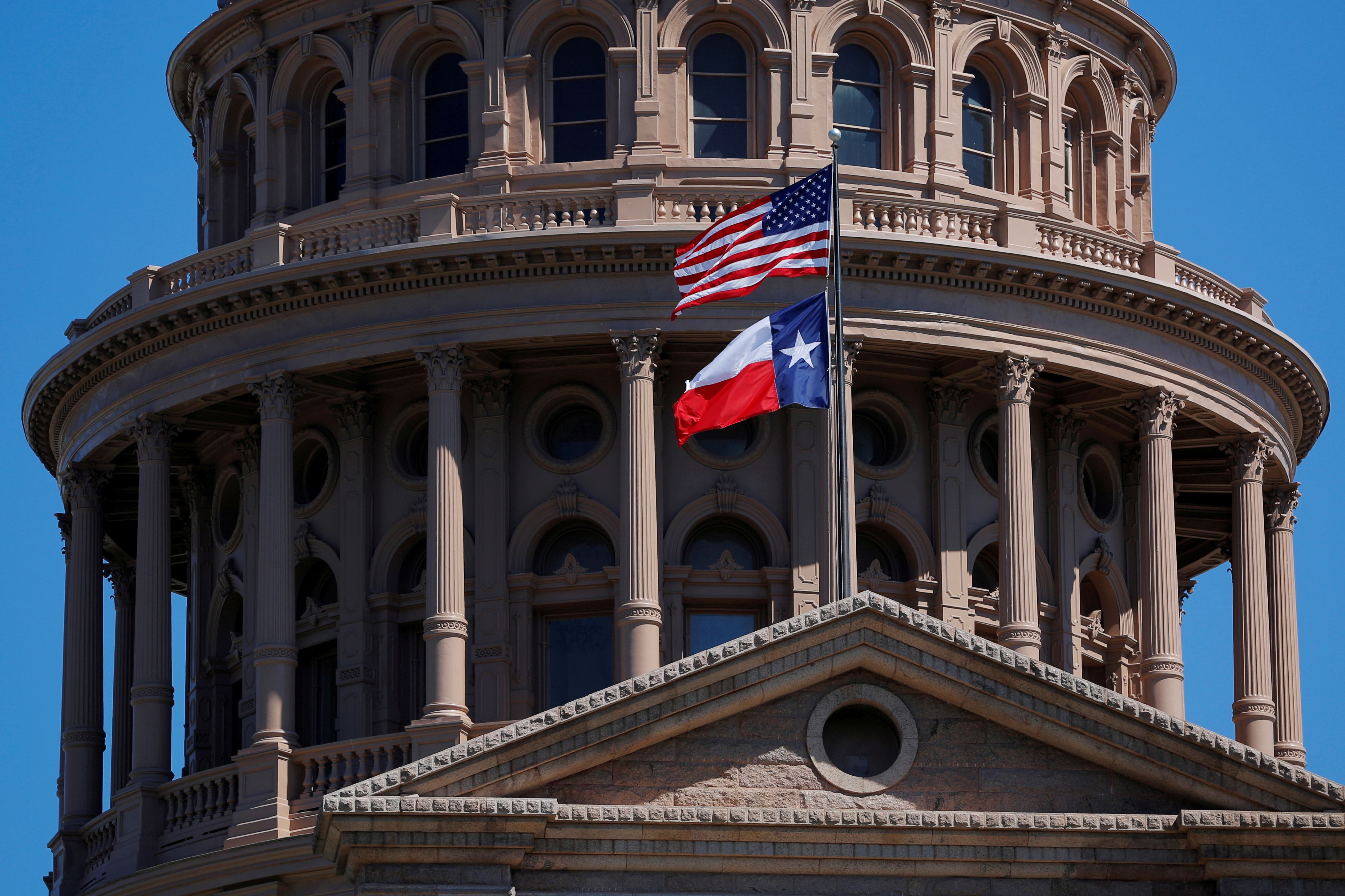 The U.S flag and the Texas State flag fly over the Texas State Capitol in Austin, Texas, U.S., March 14, 2017. REUTERS/Brian Snyder/File Photo