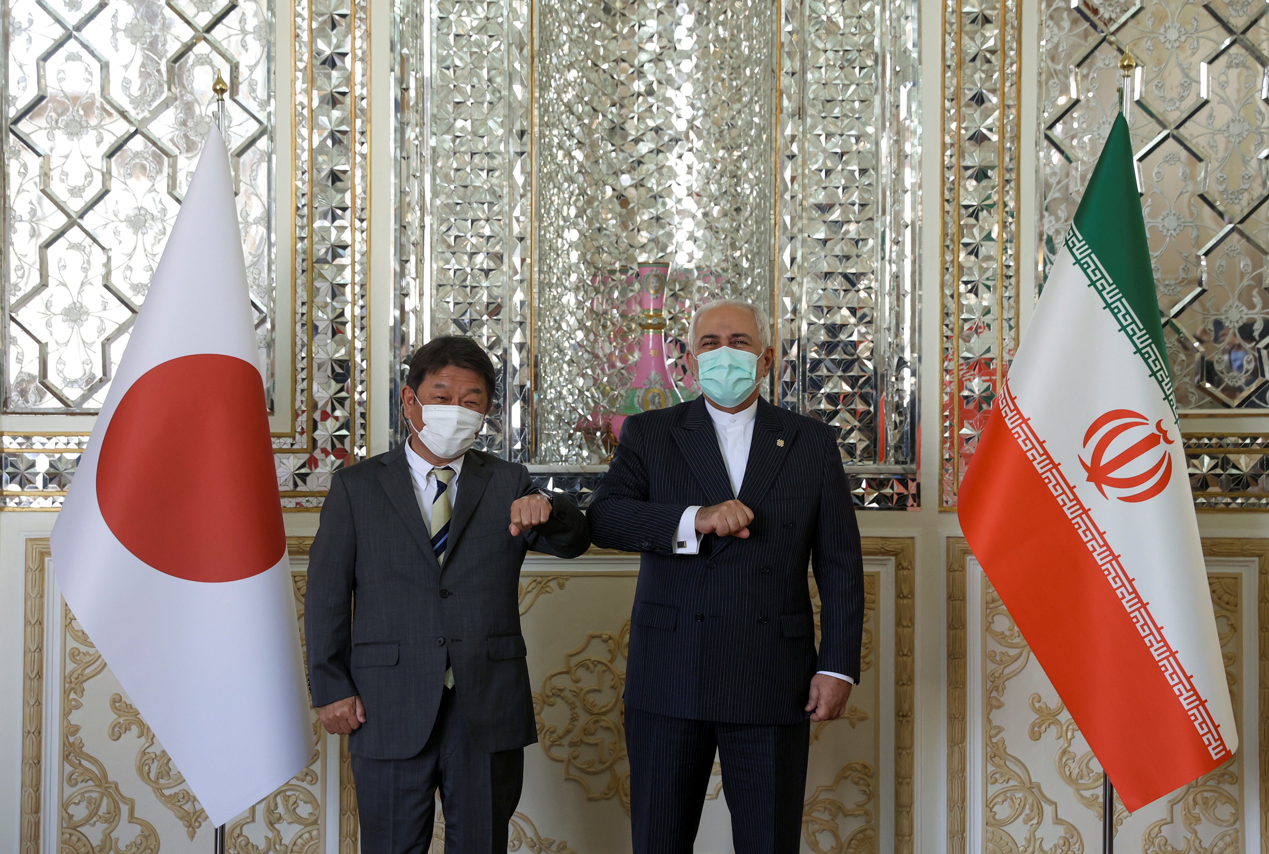 Iran's Foreign Minister Mohammad Javad Zarif and Japanese Foreign Minister Toshimitsu Motegi bump elbows during a meeting in Tehran, Iran August 22, 2021. Majid Asgaripour/WANA (West Asia News Agency) via REUTERS