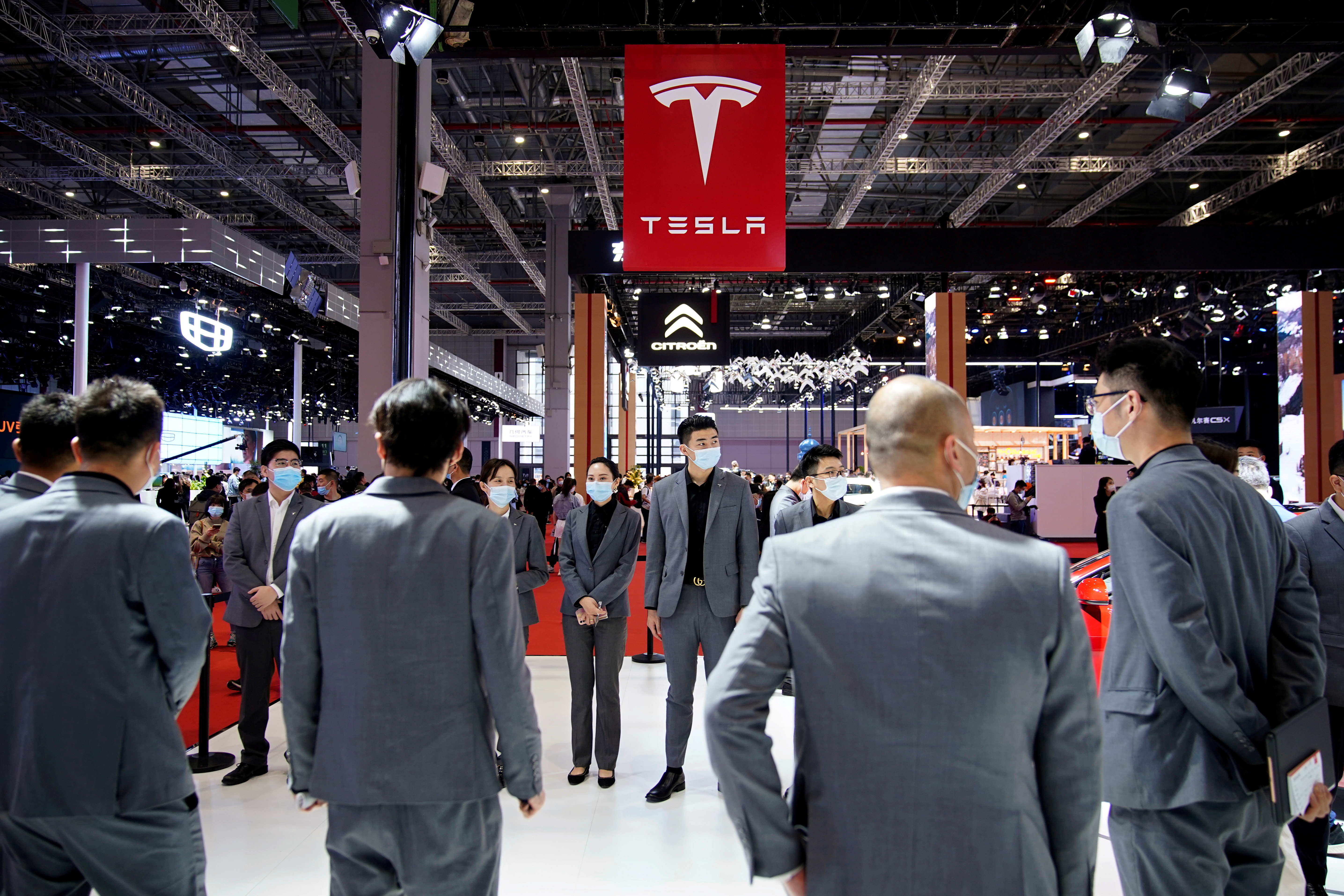 Staff members stand at the Tesla booth during a media day for the Auto Shanghai show in Shanghai, China April 19, 2021. REUTERS/Aly Song