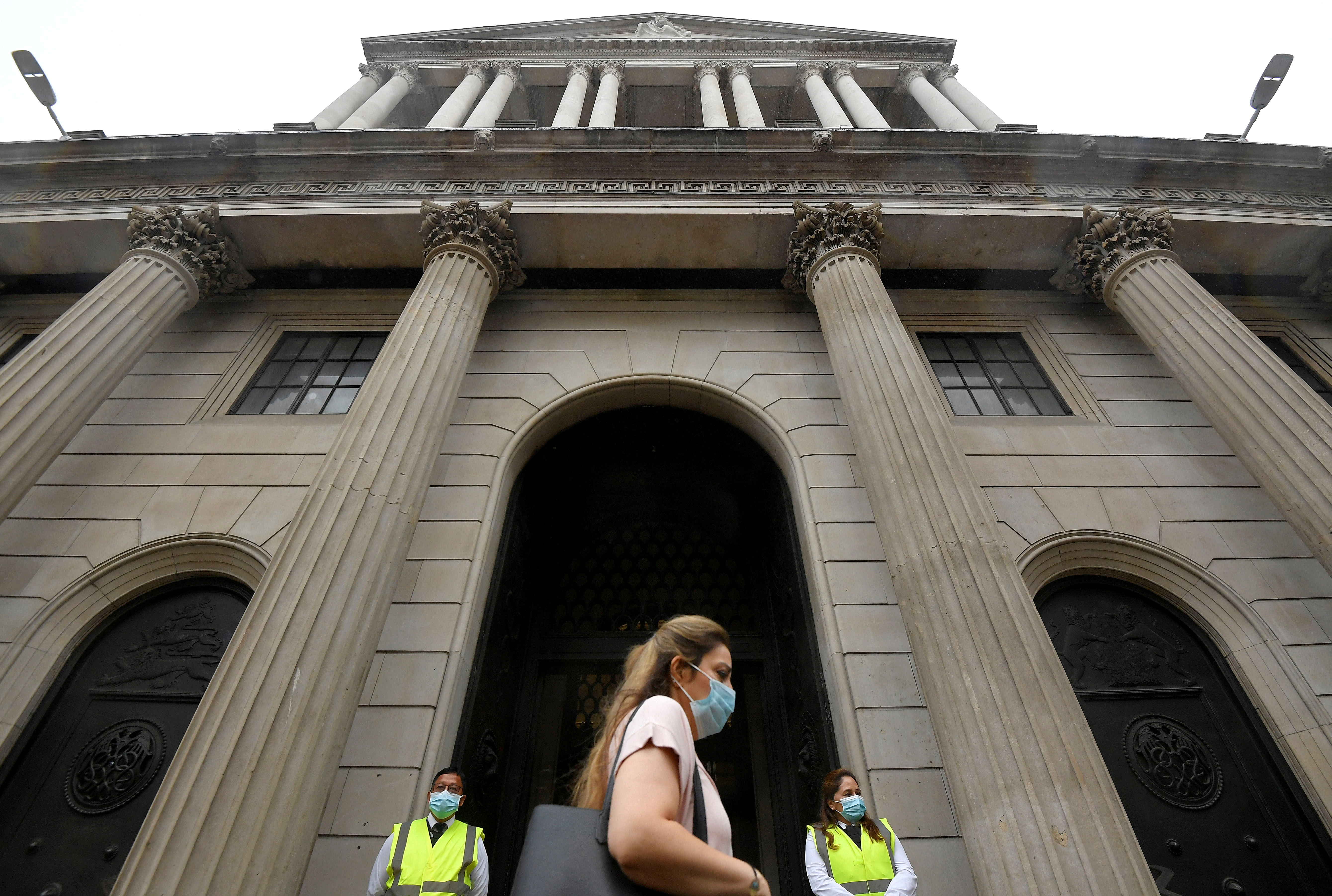 A worker wearing a protective face mask walks past the Bank of England in the City of London, Britain, August 6, 2020. REUTERS/Toby Melville