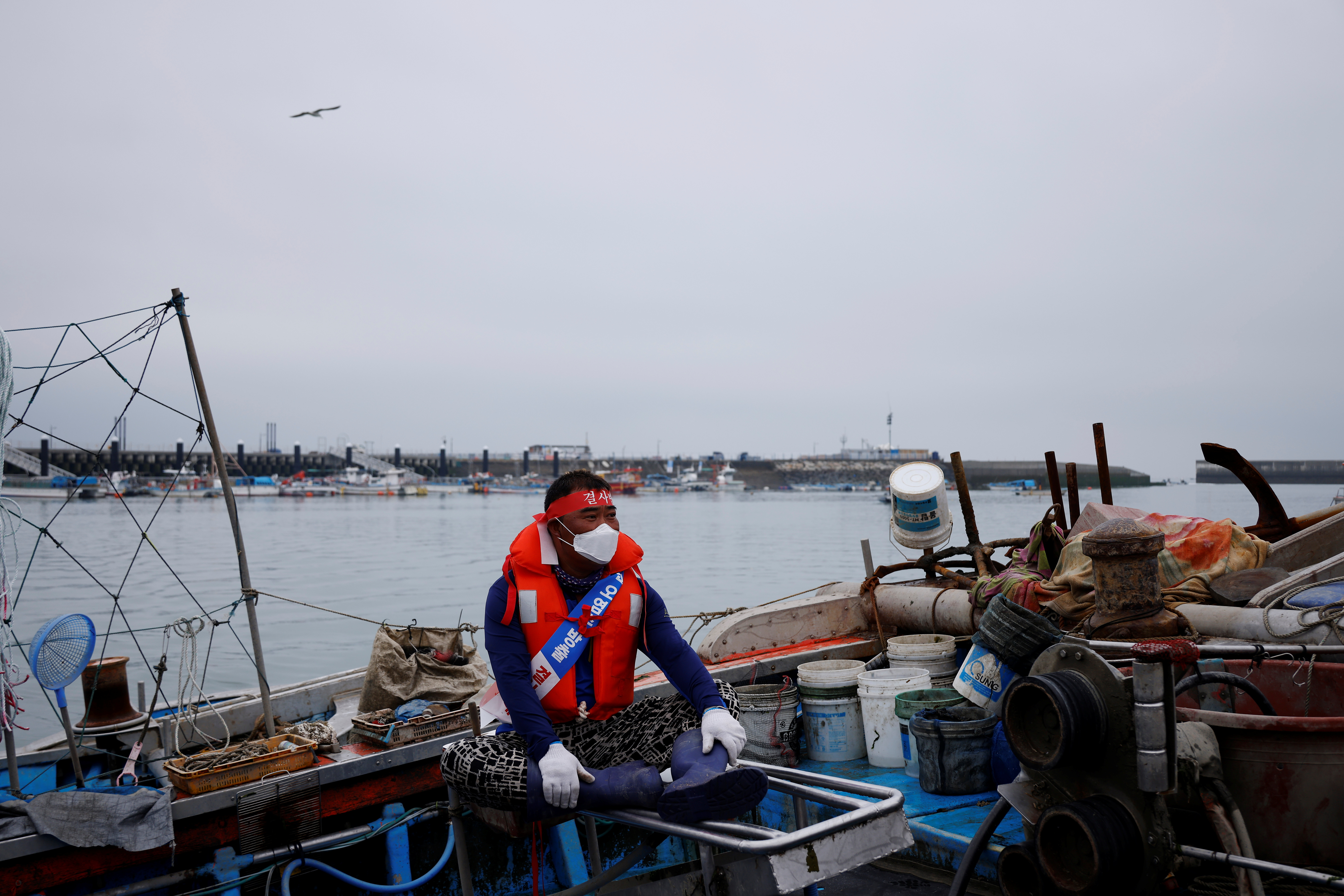 A South Korean fisherman sits on his boat during a marine protest, part of nationwide protests to demand Japan withdraw its decision to release contaminated water from its crippled Fukushima nuclear plant into the sea, at the sea off Incheon, South Korea, April 30, 2021.  REUTERS/Kim Hong-Ji