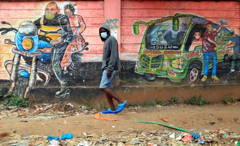 A man wears a face mask as he walks past a wall mural advocating against the coronavirus disease (COVID-19) outbreak within the Kibera settlement in Nairobi, Kenya July 18, 2021. Picture taken July 18, 2021. REUTERS/Thomas Mukoya