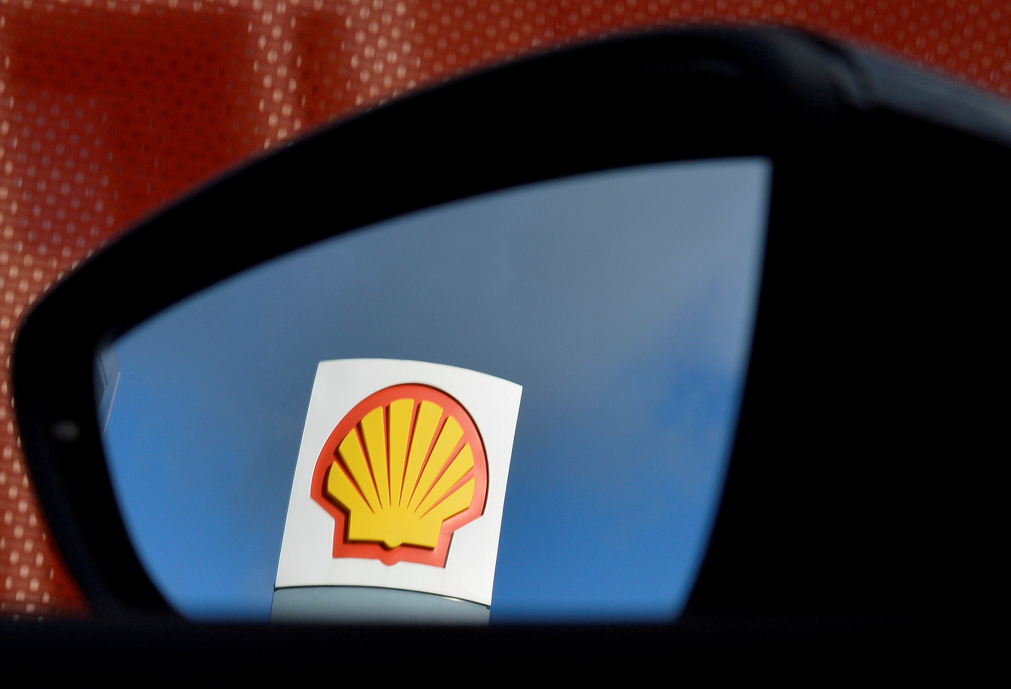 A Shell logo is seen reflected in a car's side mirror at a petrol station in west London, Britain, January 29, 2015. REUTERS/Toby Melville