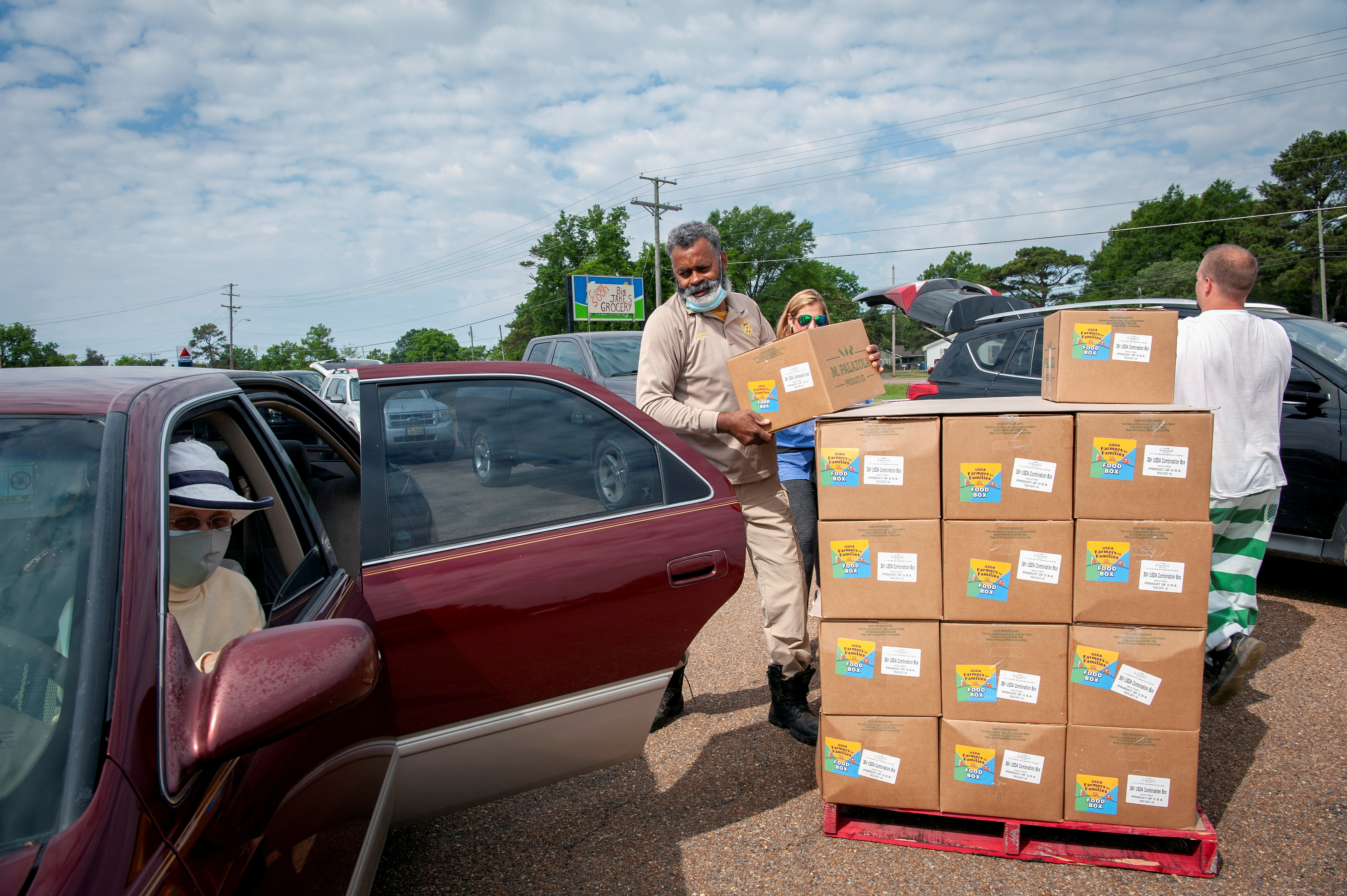 A Quitman County Sheriff's Department officer distributes food boxes at an aid site in Marks, Mississippi, U.S., May 24, 2021.  REUTERS/Rory Doyle
