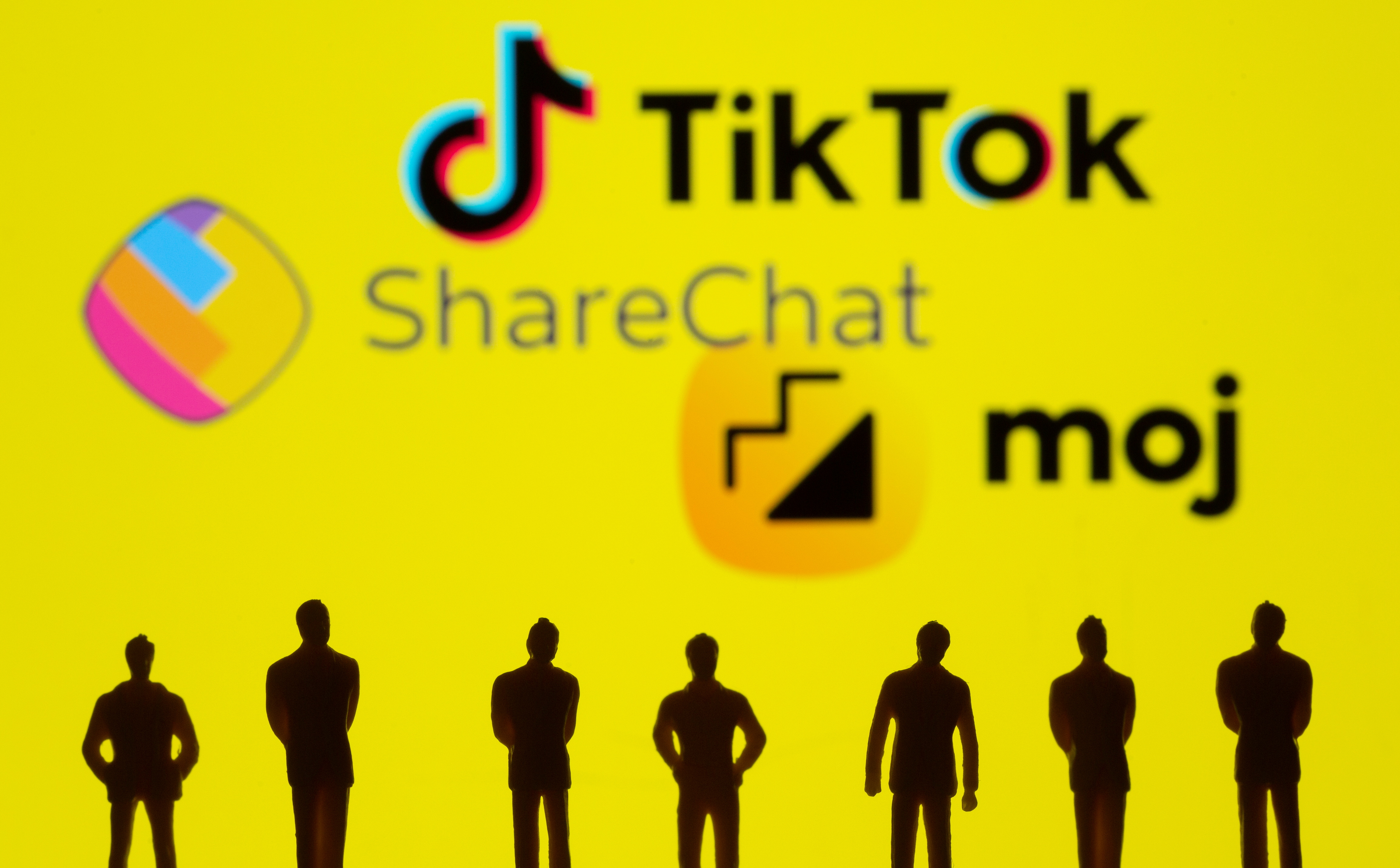Small toy figures are seen in front of displayed TikTok, ShareChat and Moj logo in this illustration taken, July 26, 2021. REUTERS/Dado Ruvic/Illustration