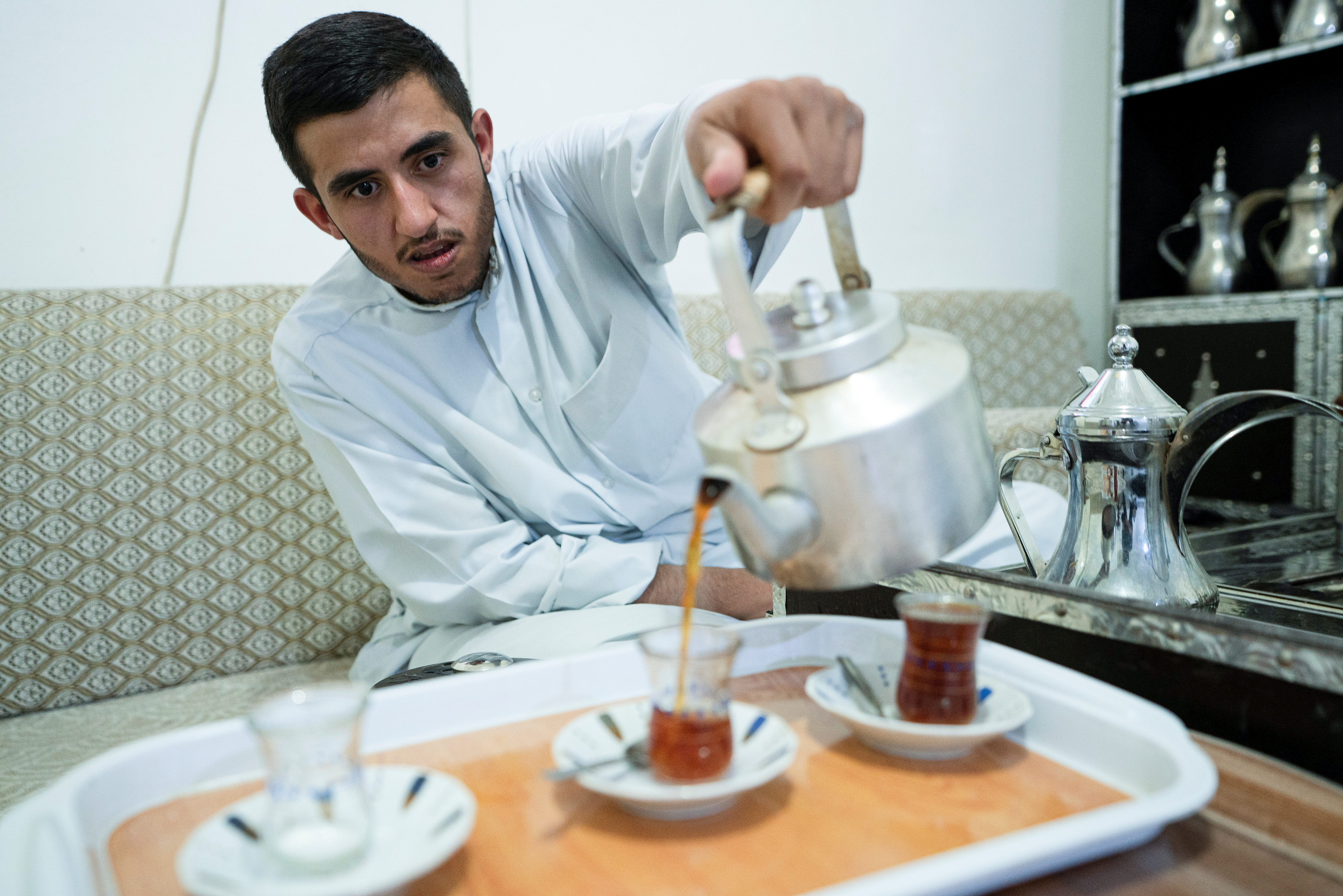 Ahmad al-Enezi, a stateless frontline worker pours tea at his home in Sulaibiya, Kuwait September 6,2021. REUTERS/Stephanie McGehee