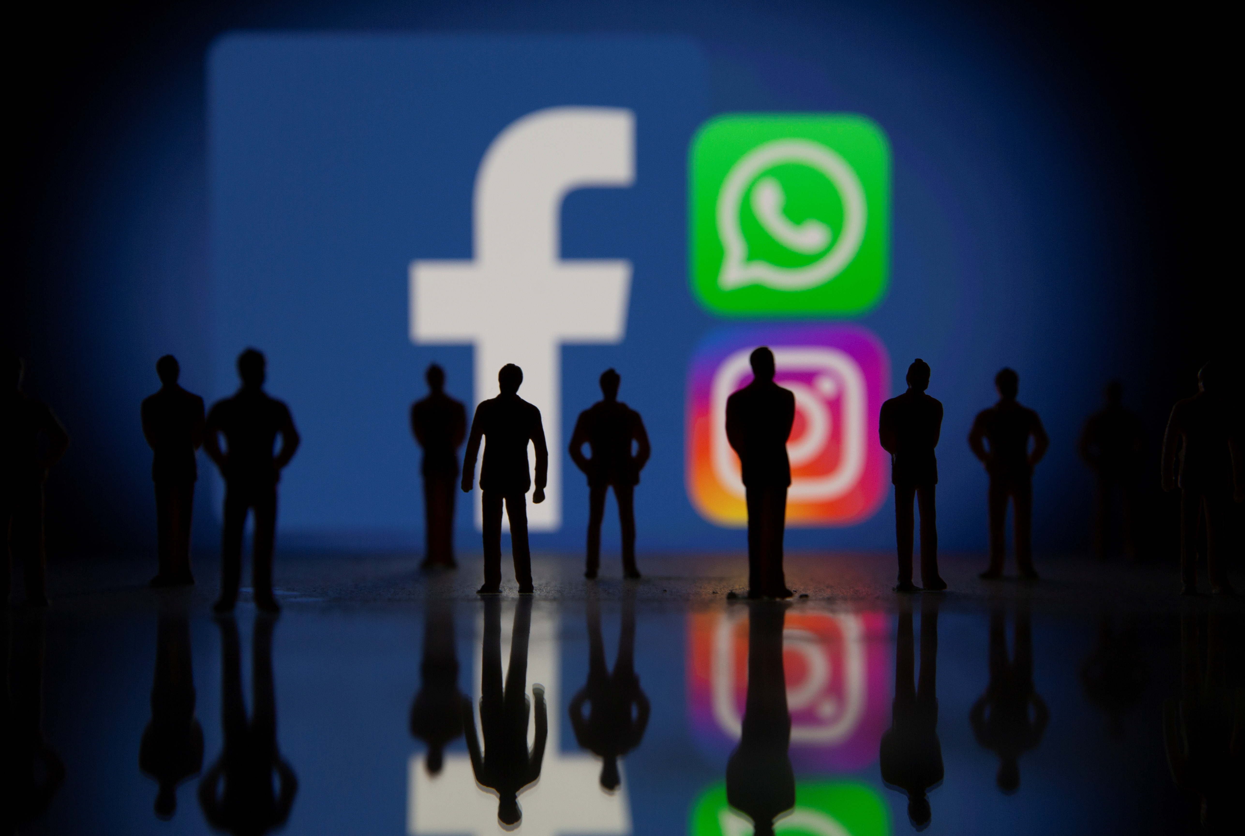 Small toy figures are seen in front of displayed Facebook, Whatsapp and Instagram logos in this illustration taken October 4, 2021. REUTERS/Dado Ruvic/Illustration