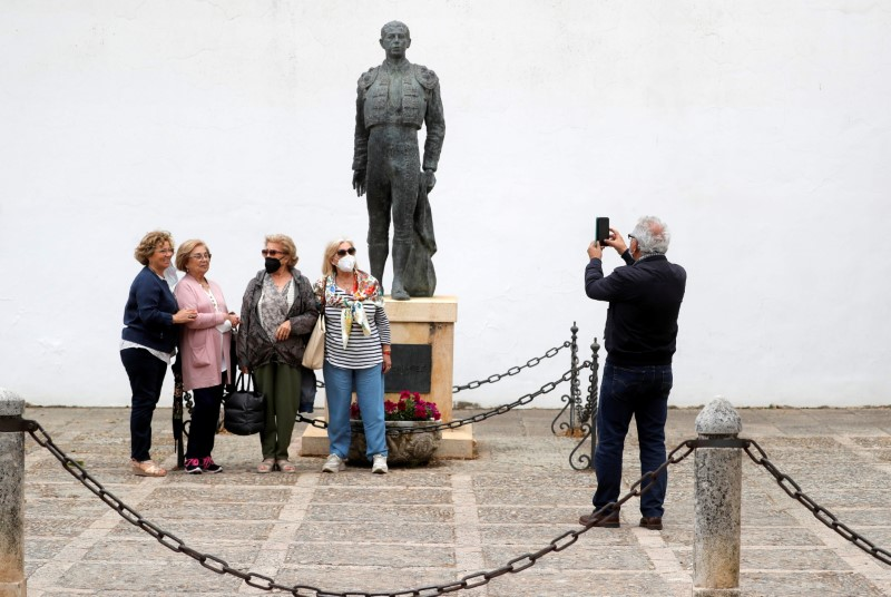 Іспанські туристи знімають захисні маски, щоб сфотографуватися зі статуєю тореадора біля арени для кориди, після того, як прем'єр-міністр Іспанії Педро Санчес заявив у п'ятницю про скасування загального зобов'язання носити маски на відкритому повітрі з 26 червня на тлі коронавірусної хвороби (COVID -19) пандемія, в Ронді, Іспанія, 18 червня 2021 р. REUTERS / Jon Nazca